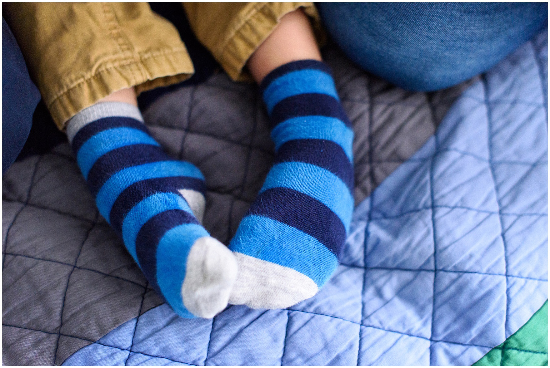 Close up of a little boy's feet in striped socks during an at home family session.