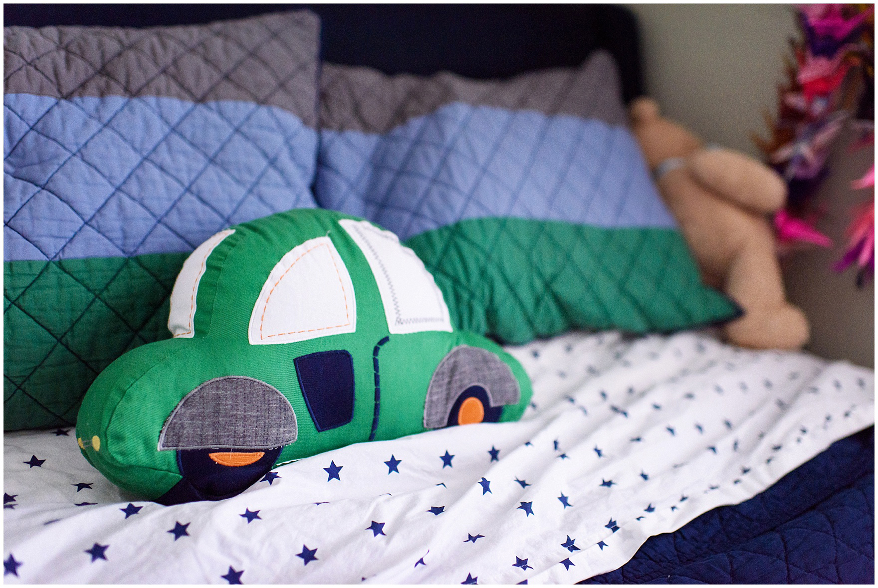 Cute detail of a car pillow and boys bedding during an at home family session.