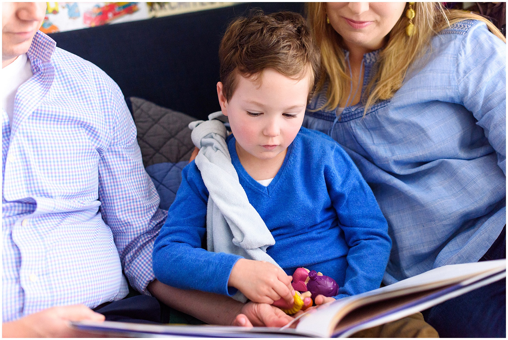 Mom and dad snuggle and read with their son during an at home family session.