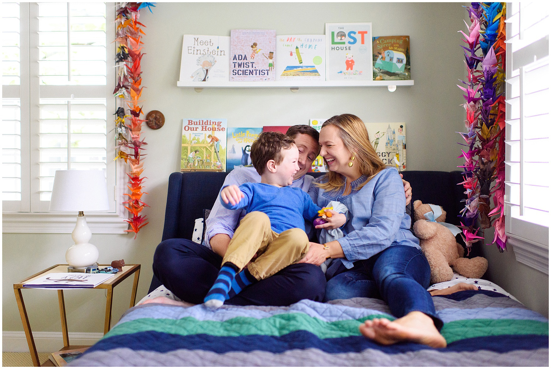 A family laughs and cuddles during an at home family session.