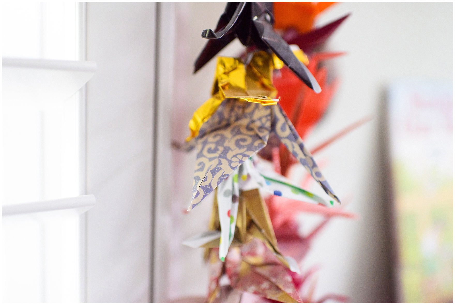 Detail of an origami crane, part of a garland of a thousand paper cranes, during an at home family session.