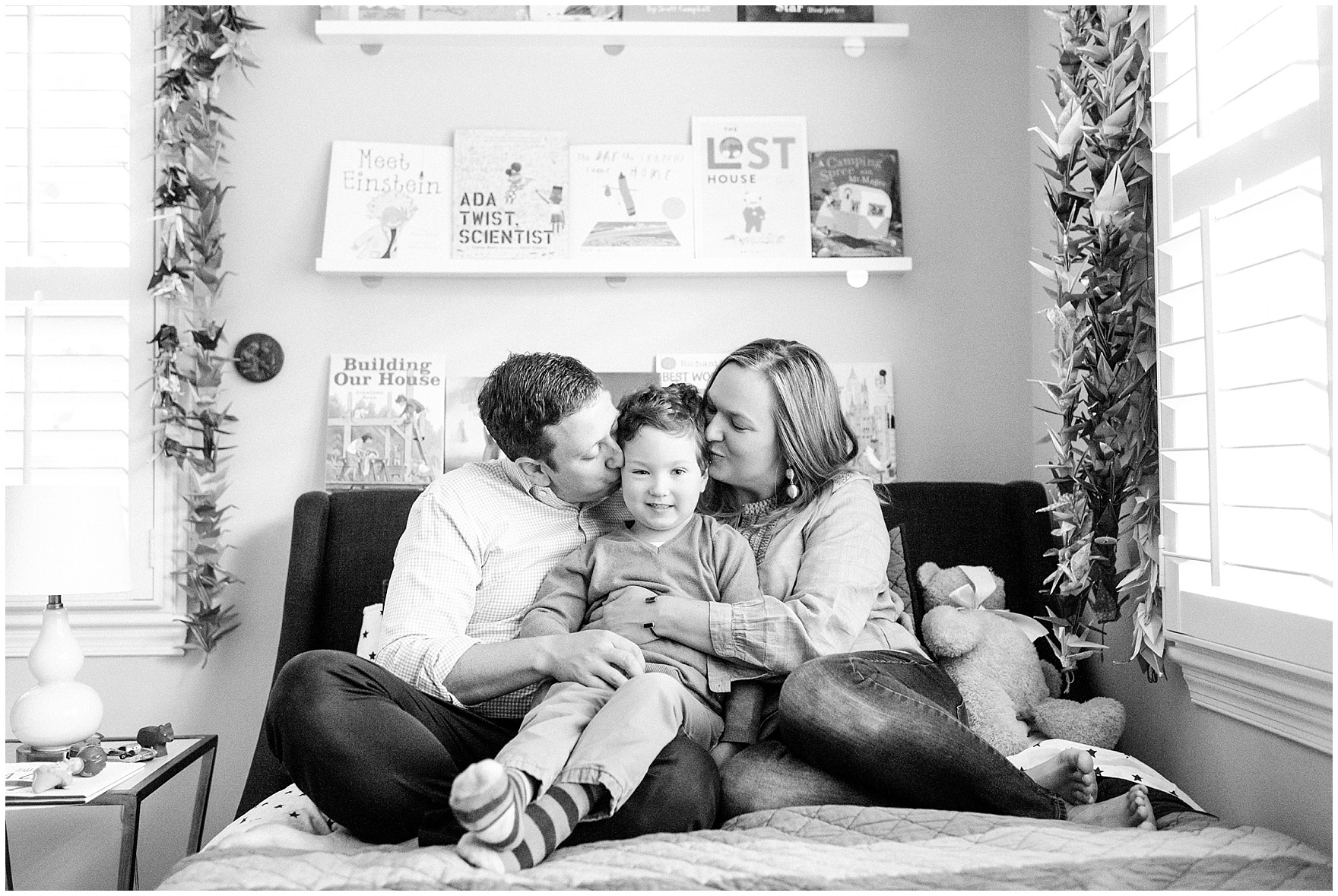 Mom and dad kiss their son during an at home family session.