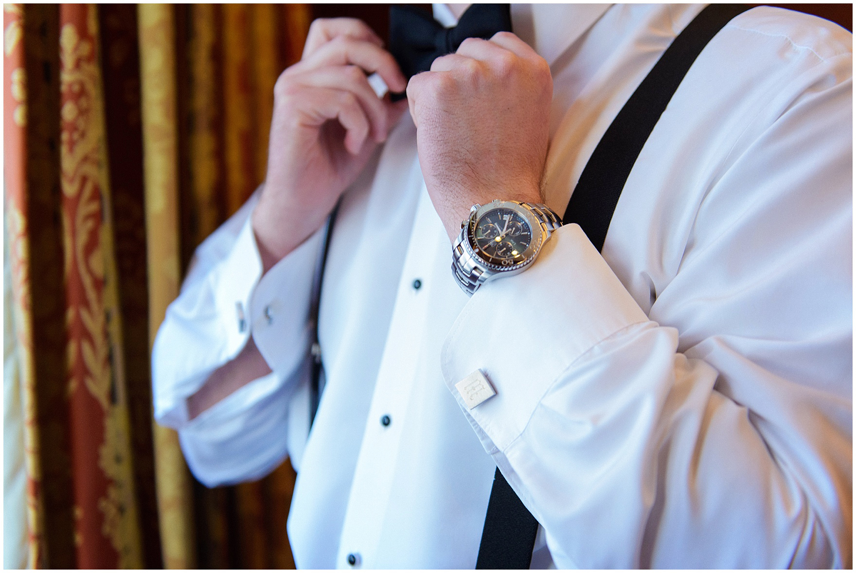 The groom ties his bow tie before his University Club of Chicago wedding.