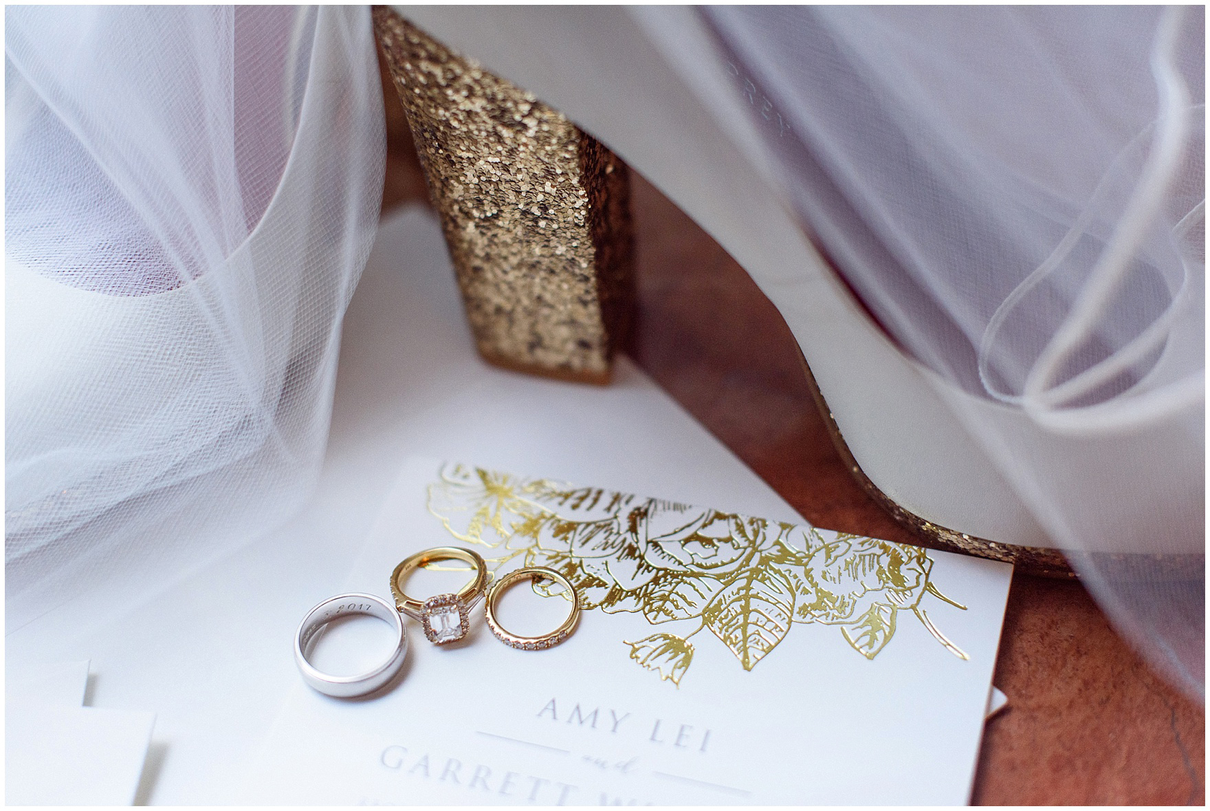 Wedding and engagement rings sit on a gold foil invitation for a University Club of Chicago wedding.