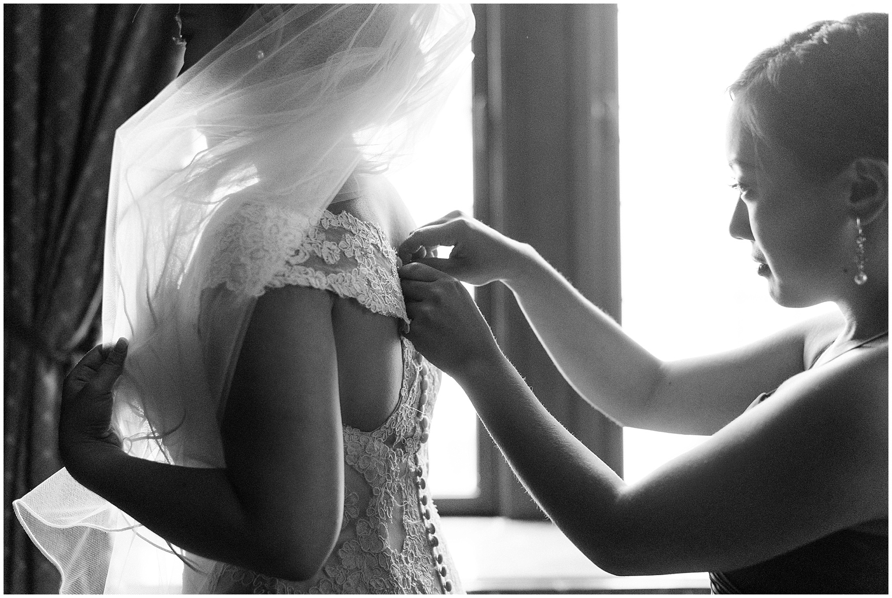 The bride gets buttoned into her lace gown for a University Club of Chicago wedding.
