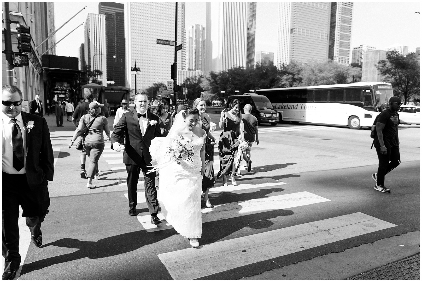 The bride and groom walk with their wedding party down Michigan Avenue before their University Club of Chicago wedding.