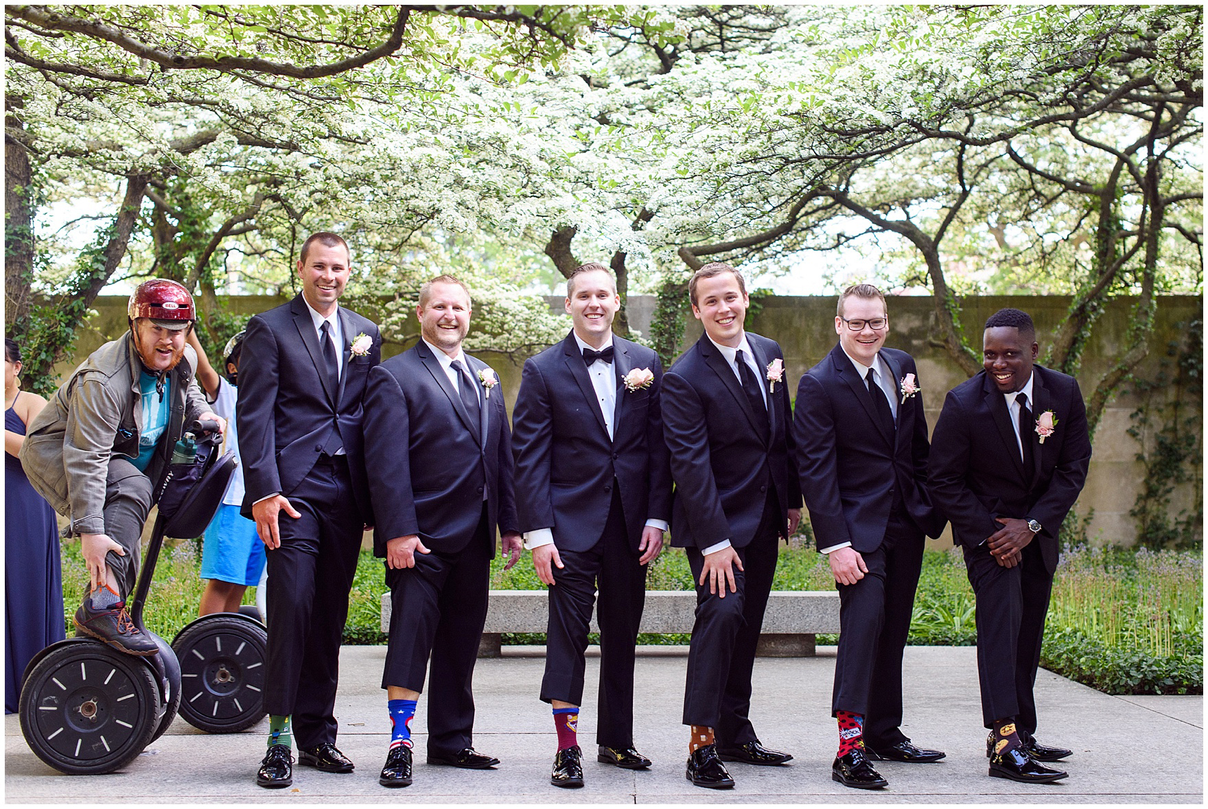 Groomsmen get photobombed by a tourist on a segway while posing in the South Gardens of the Art Institute of Chicago before a University Club of Chicago wedding.