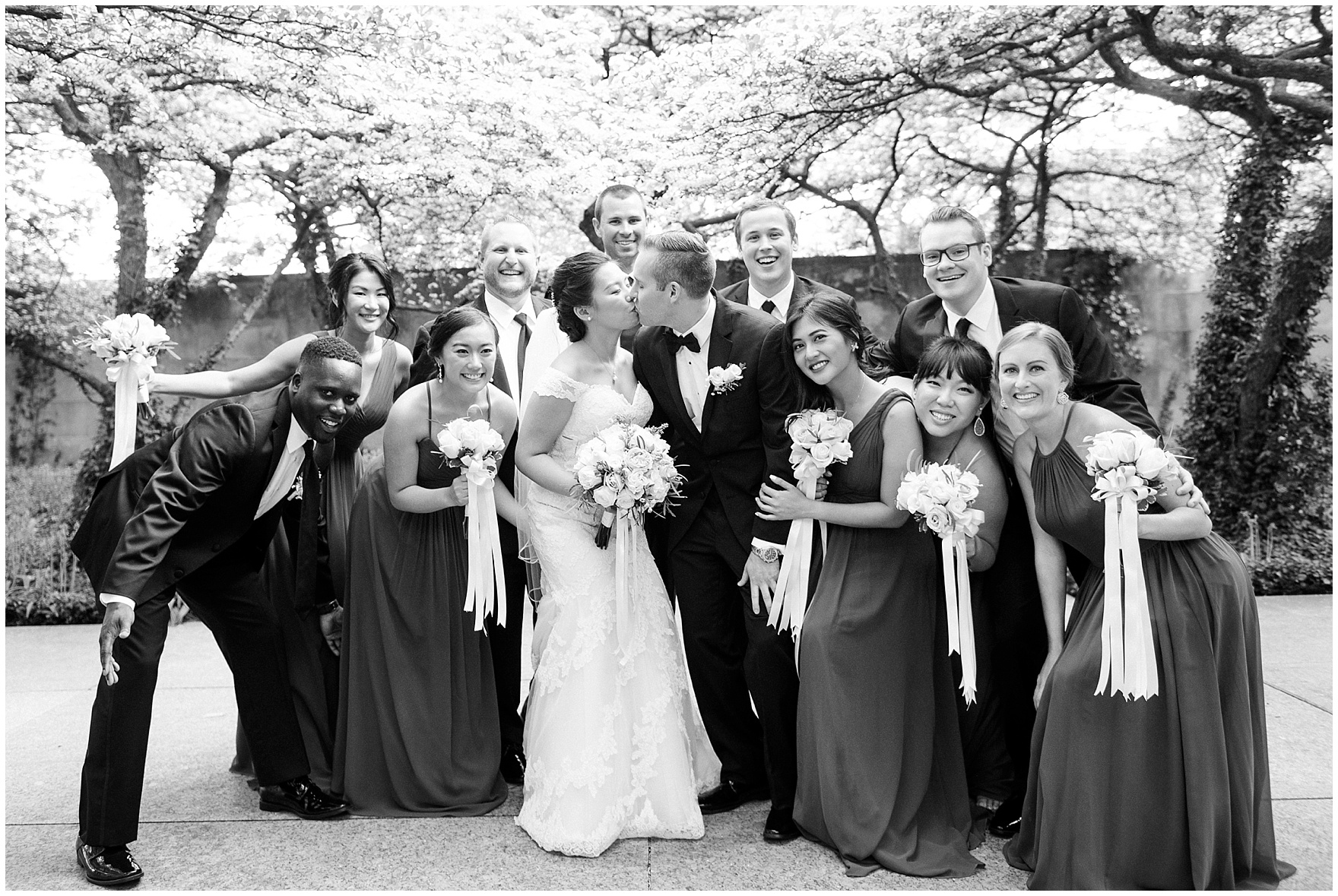 A bridal party cheers in the South Gardens of the Art Institute of Chicago before a University Club of Chicago wedding.