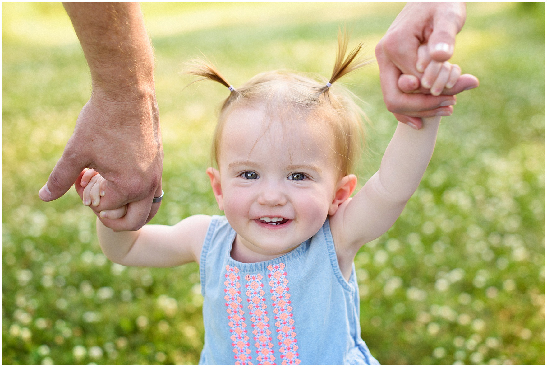 A little girl grins and holds her parents' hands during a Chicago Lincoln Park family photography session.