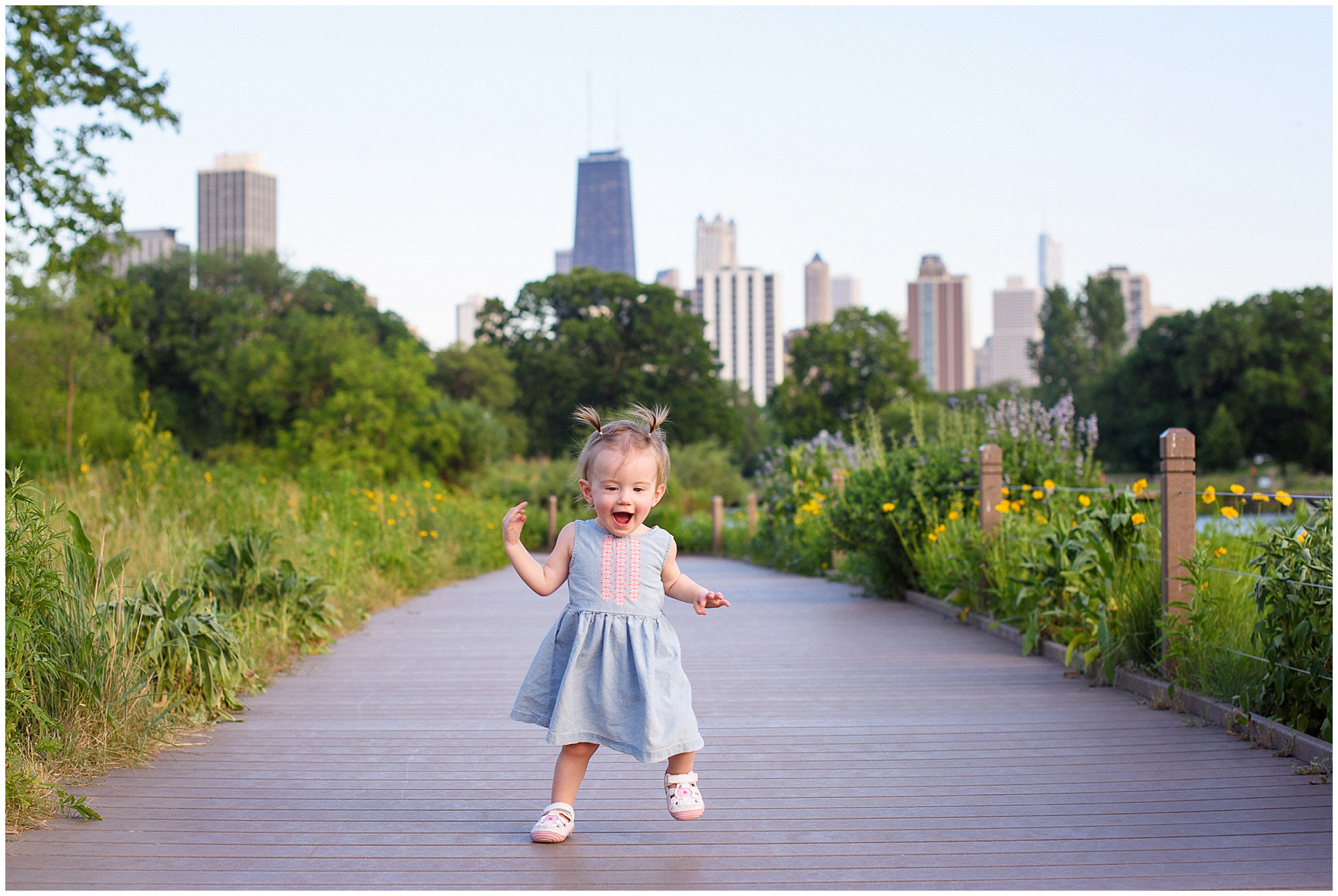 A little girl laughs and walks along the Nature Boardwalk during a Chicago Lincoln Park family photography session.