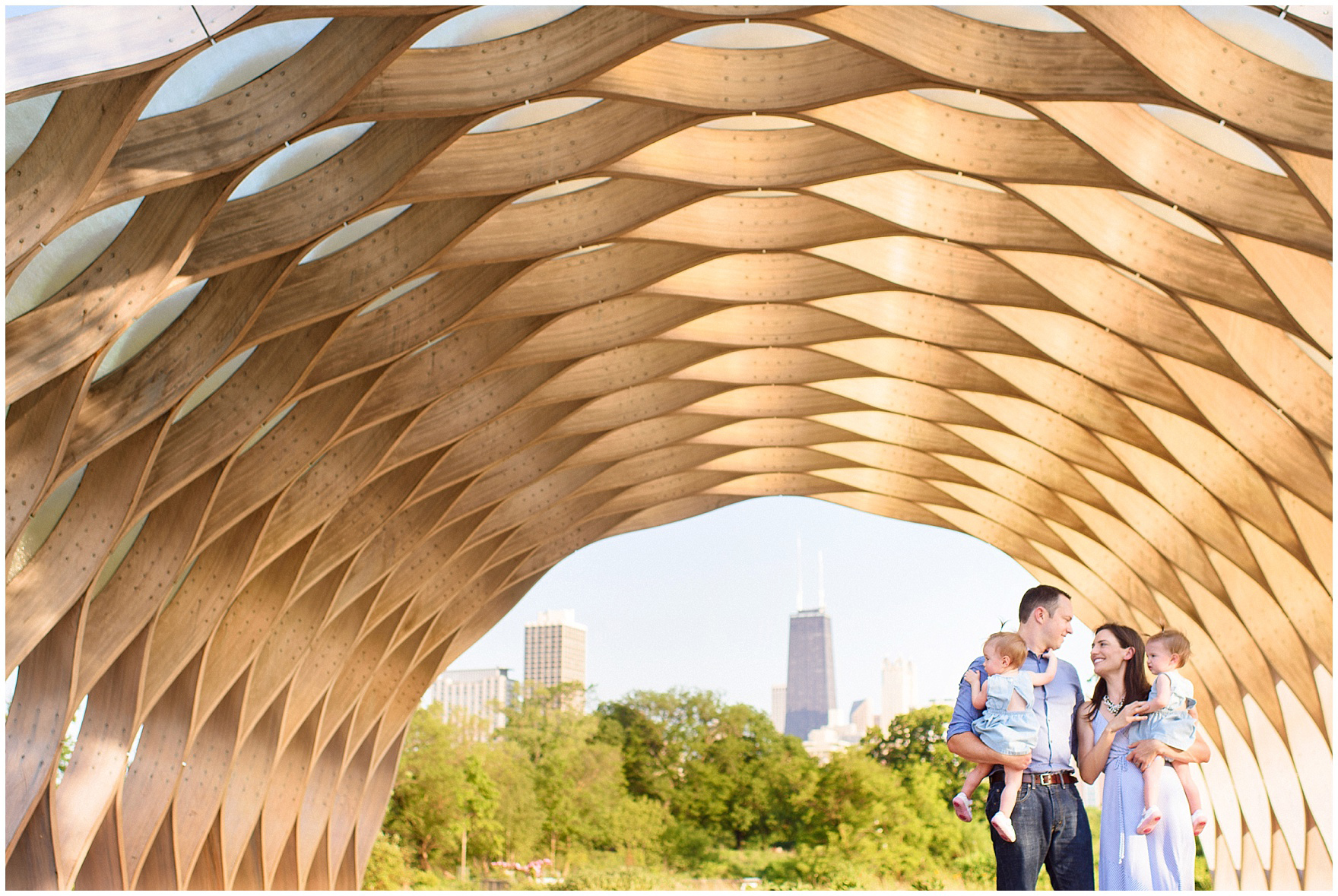 A family stands under the honeycomb during a Chicago Lincoln Park family photography session.