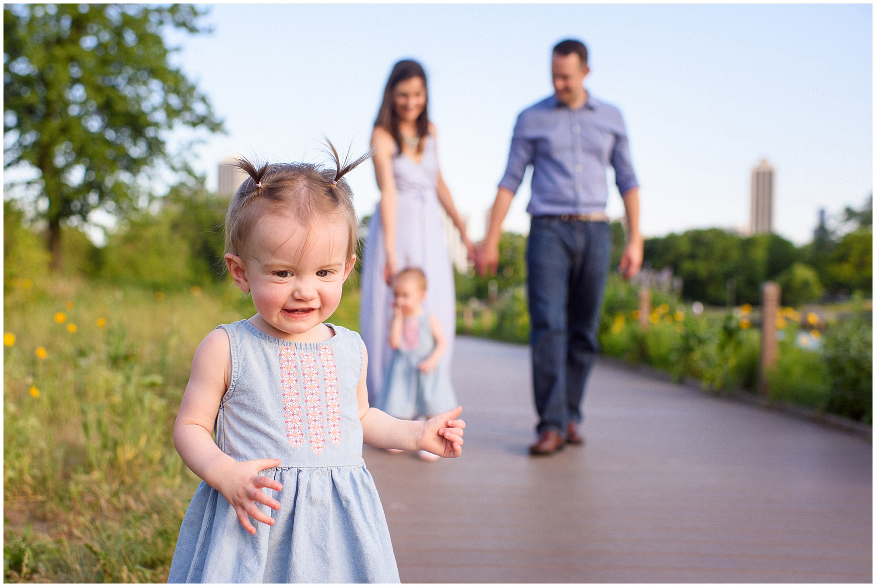 A family with twin girls walks along the Nature Boardwalk during a Chicago Lincoln Park family photography session.