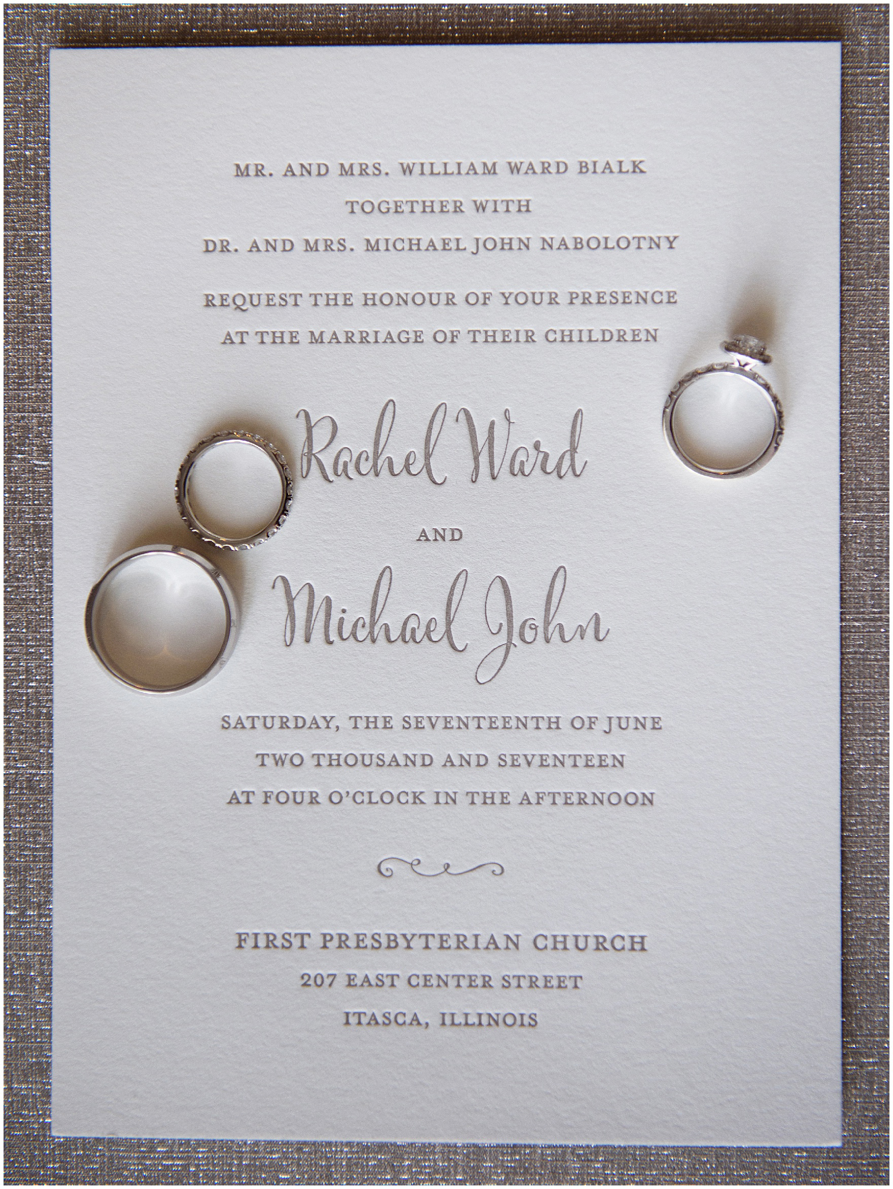 Detail photograph of a letterpress invitation with wedding bands for an Itasca Country Club Illinois wedding.
