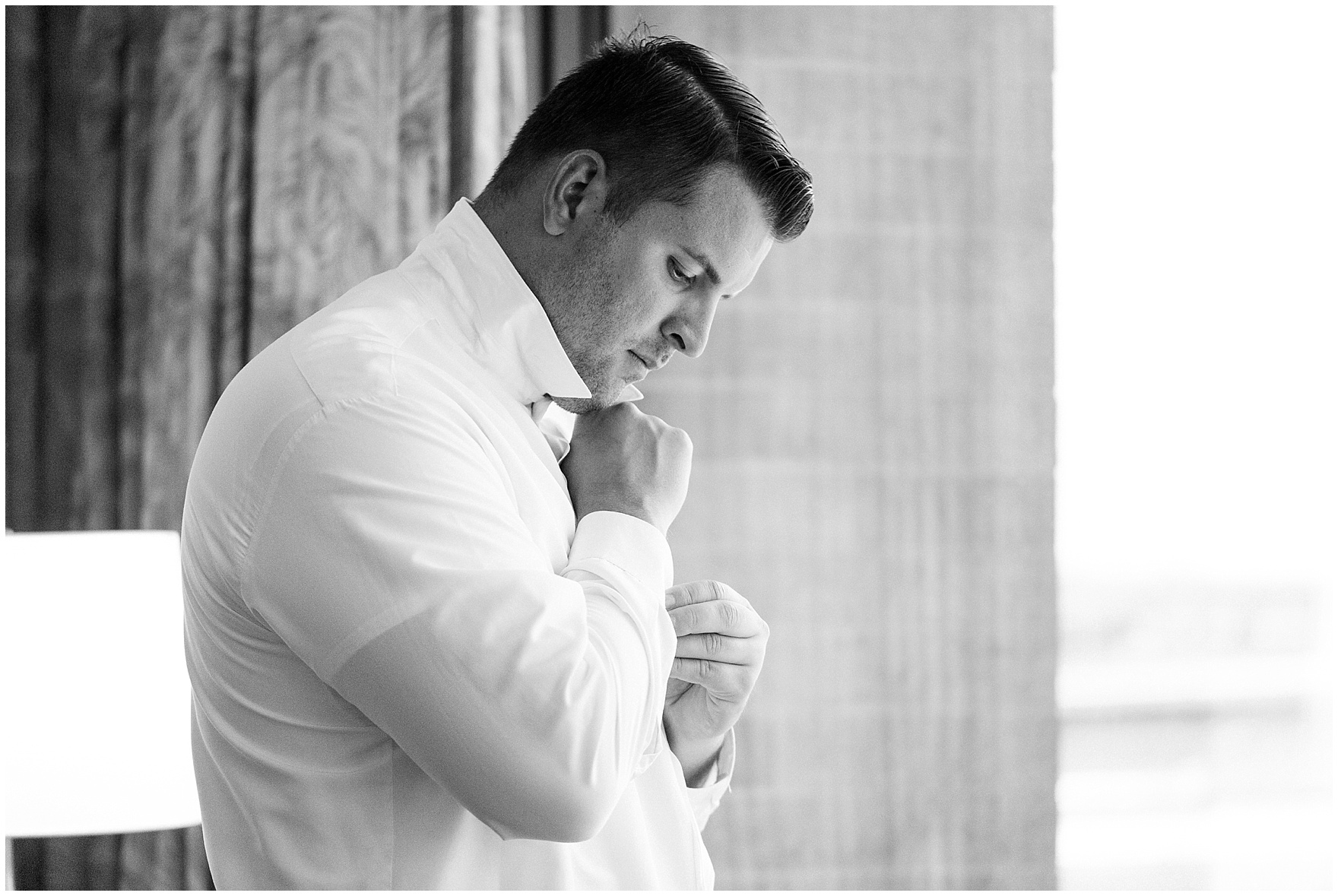 The groom fastens his cuffs while getting ready at the Westin Itasca for an Itasca Country Club Illinois wedding.