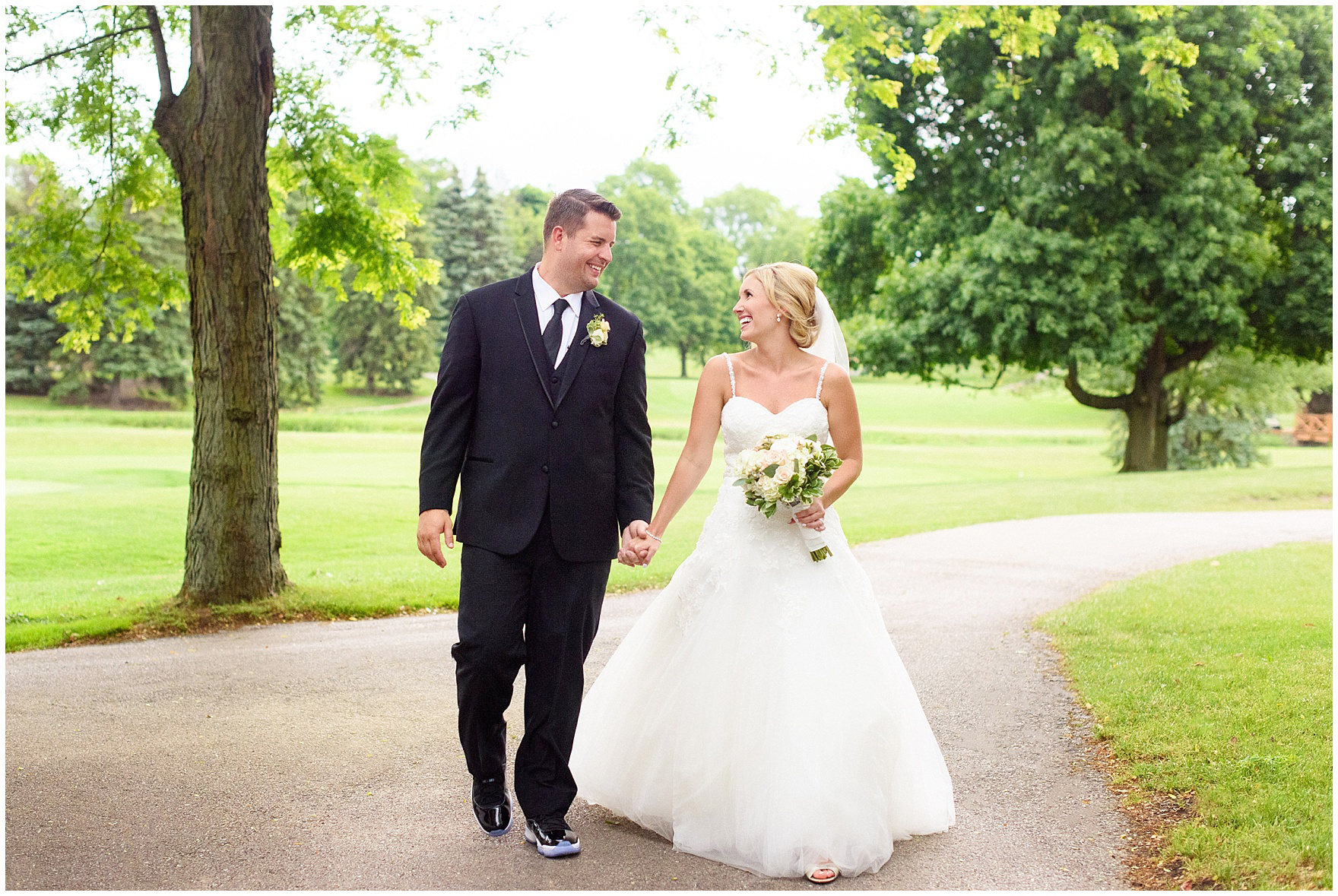 A bride and groom walk and laugh during their Itasca Country Club Illinois wedding.