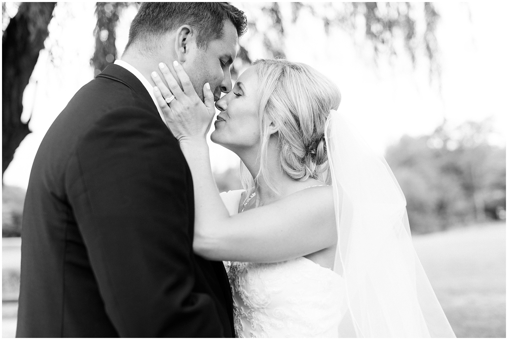 A bride and groom kiss for the camera at their Itasca Country Club Illinois wedding.