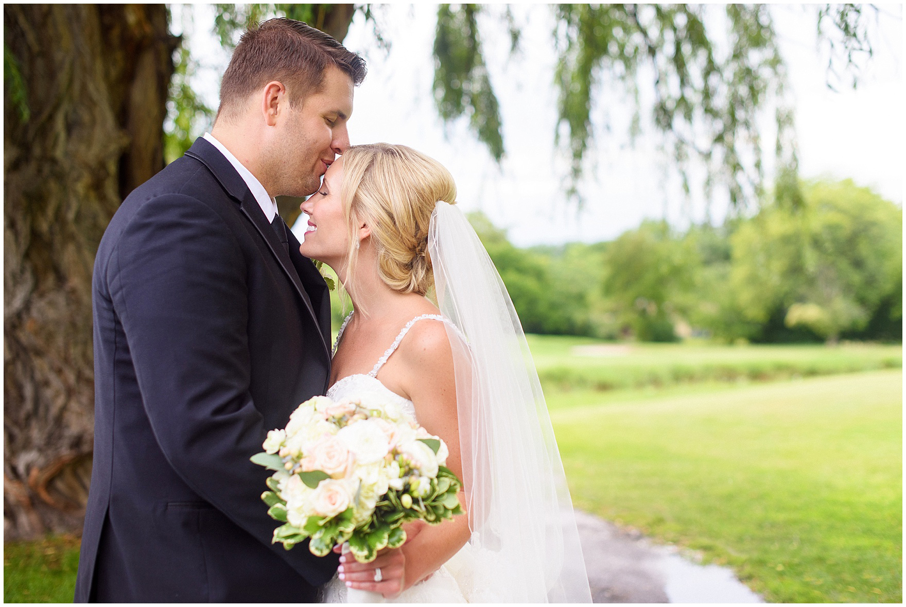 A groom kisses his bride at their Itasca Country Club Illinois wedding.