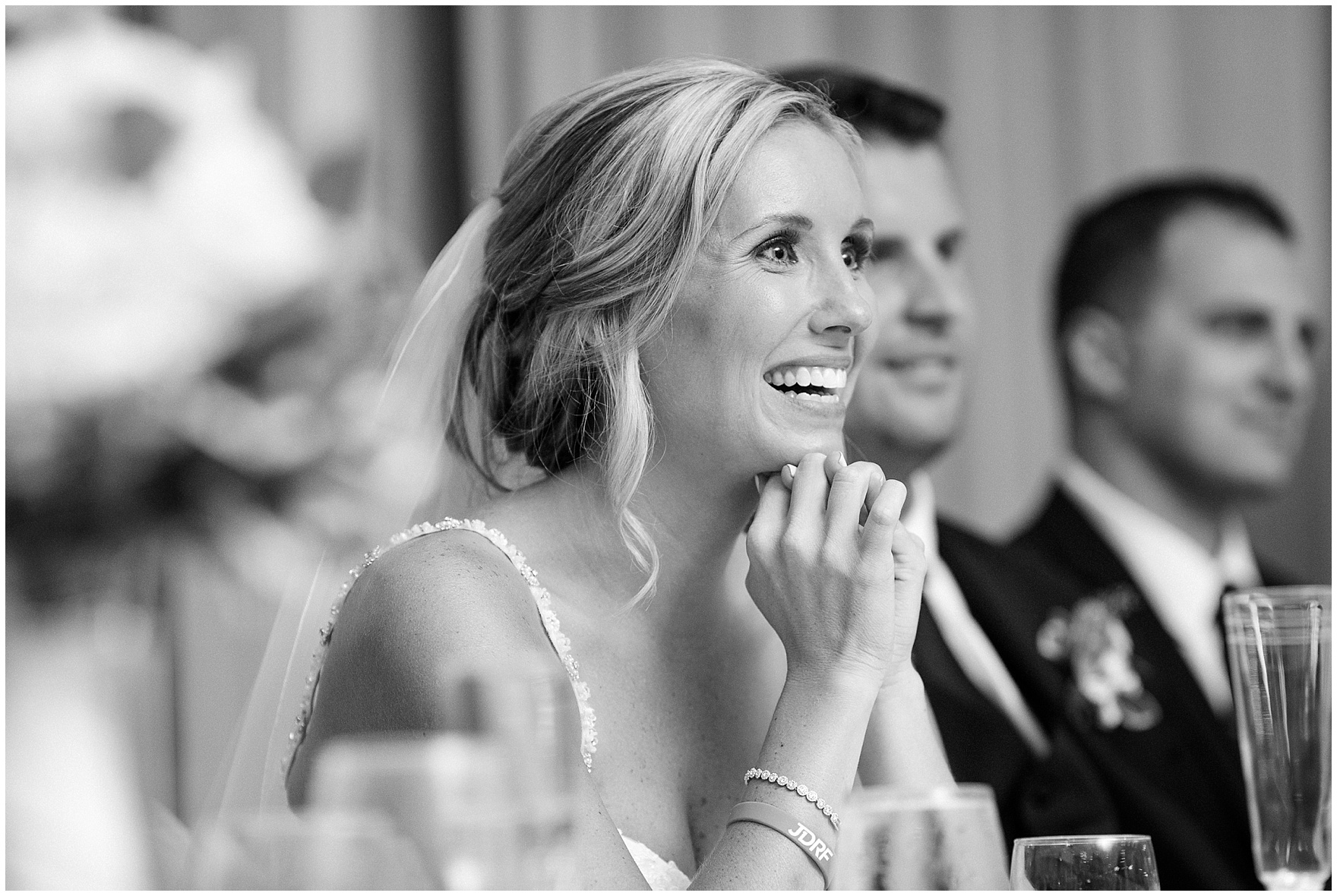 The bride listens to the maid of honor make a toast at an Itasca Country Club Illinois wedding.