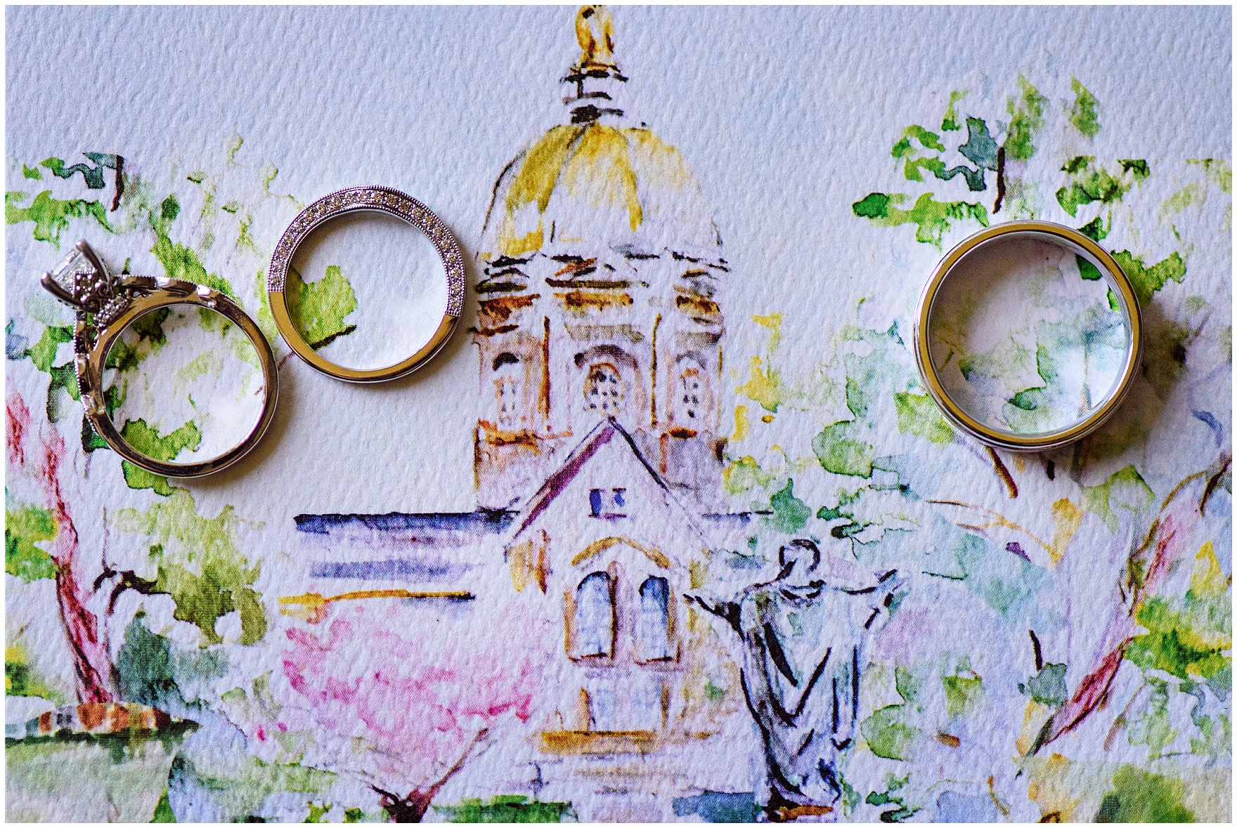 A detail shot of wedding rings on top of a custom watercolor illustration for a University of Notre Dame Wedding.