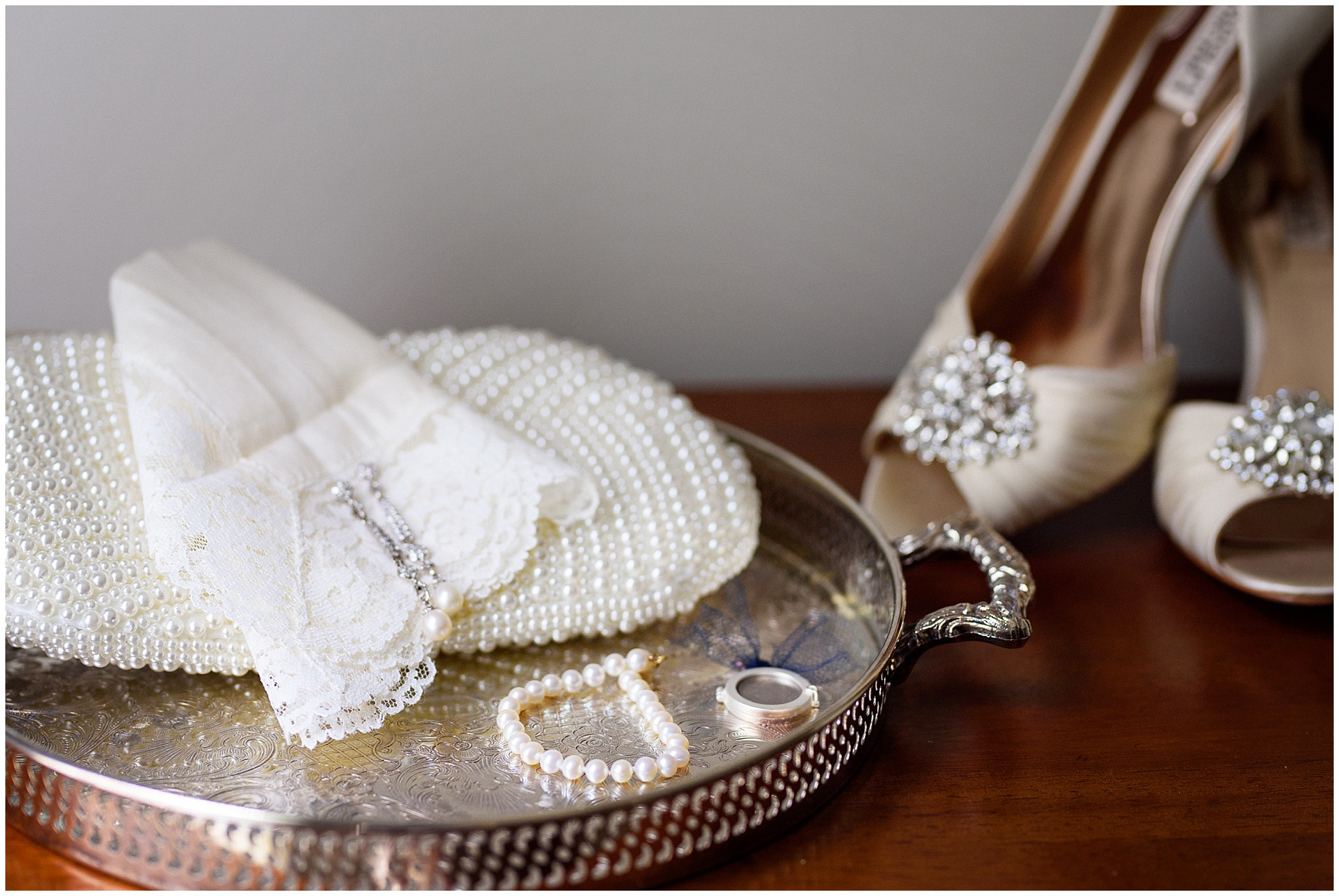 Details of a lace hankie and pearls photographed on a silver tray in the foyer of a classic home before a Biltmore Country Club Barrington wedding.