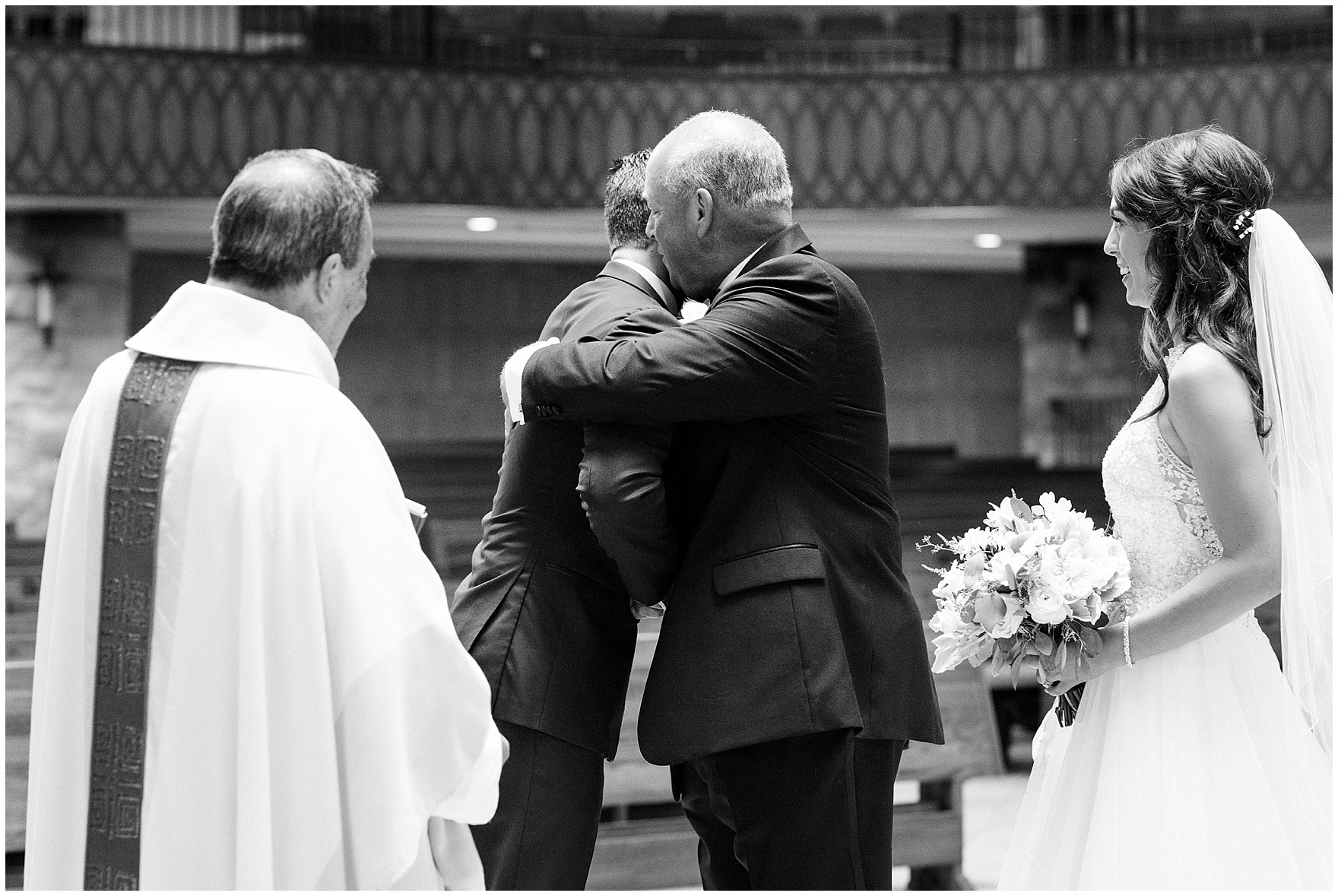 The bride's father hugs the groom during the ceremony at St. Anne's Catholic Community, for a Biltmore Country Club Barrington wedding.