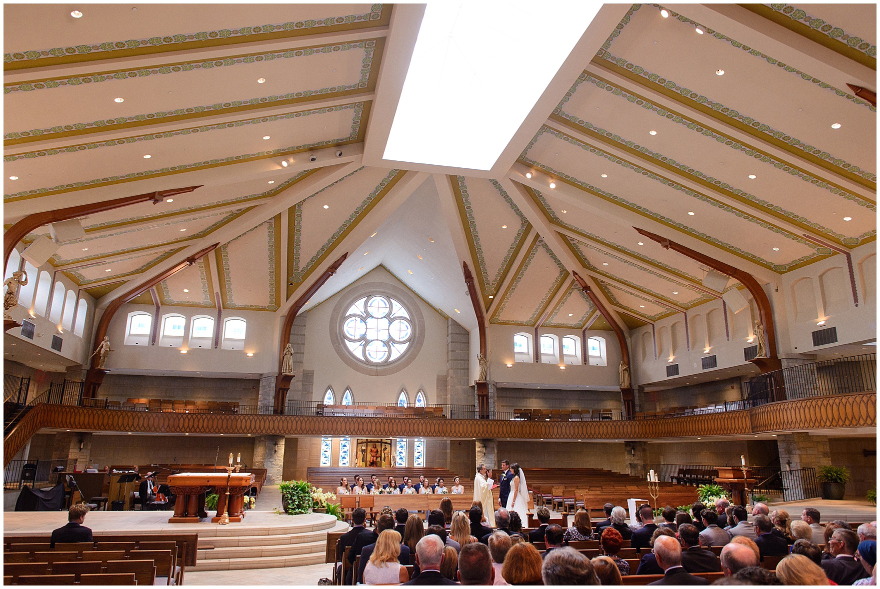 A wide shot of the beautiful church interior during the ceremony at St. Anne's Catholic Community, for a Biltmore Country Club Barrington wedding.