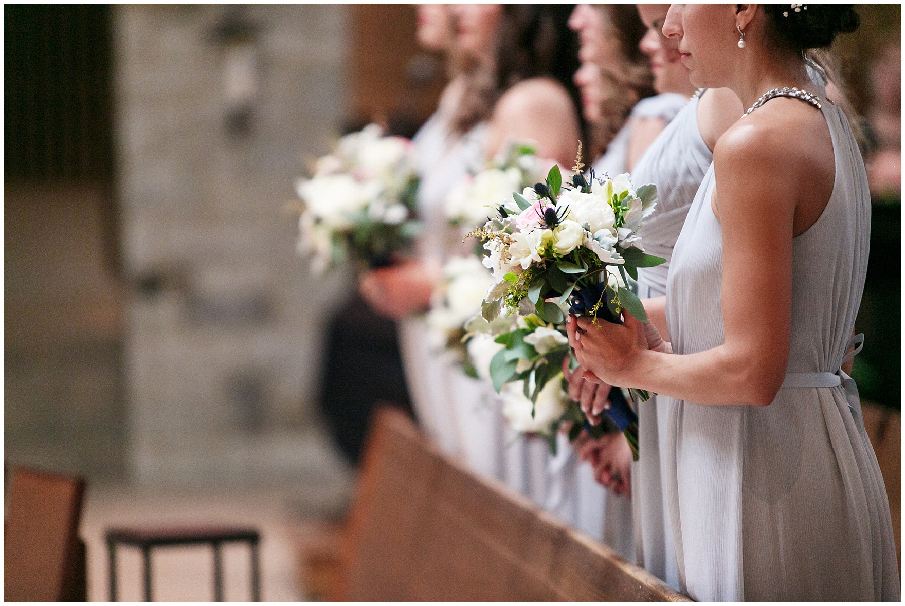 Bridesmaids stand in a line during the ceremony at St. Anne's Catholic Community, for a Biltmore Country Club Barrington wedding.