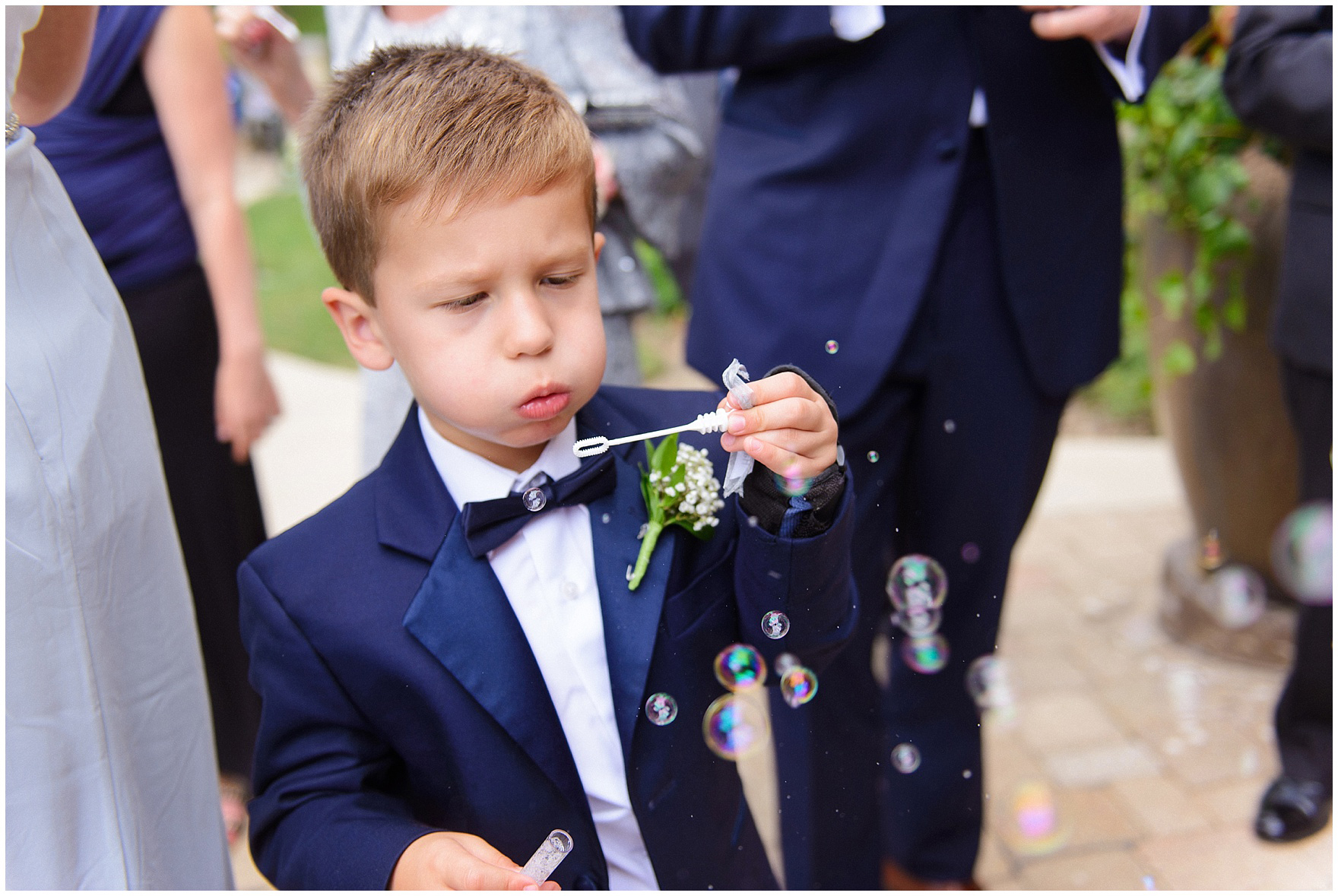 A ring bearer blows bubbles after a ceremony at St. Anne's Catholic Community, for a Biltmore Country Club Barrington wedding.