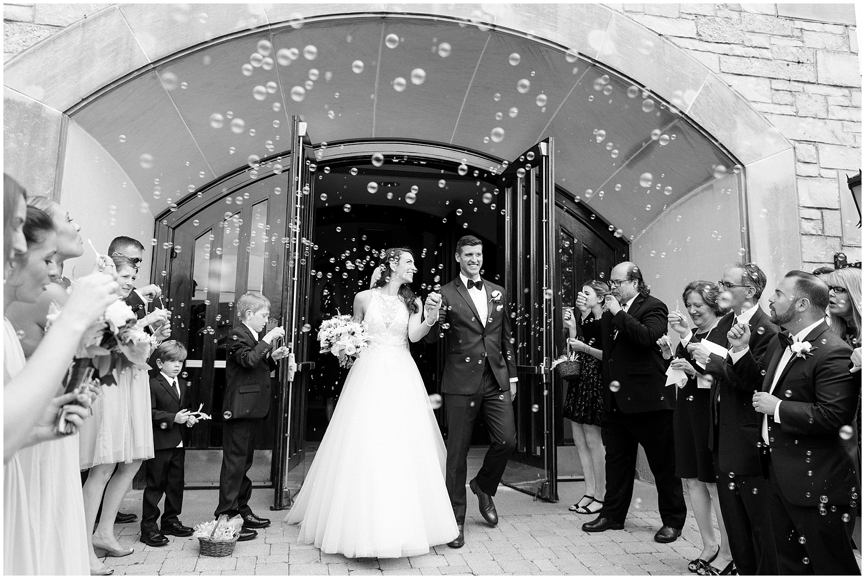 The bride and groom exit under a flurry of bubbles after their ceremony at St. Anne's Catholic Community, for a Biltmore Country Club Barrington wedding.