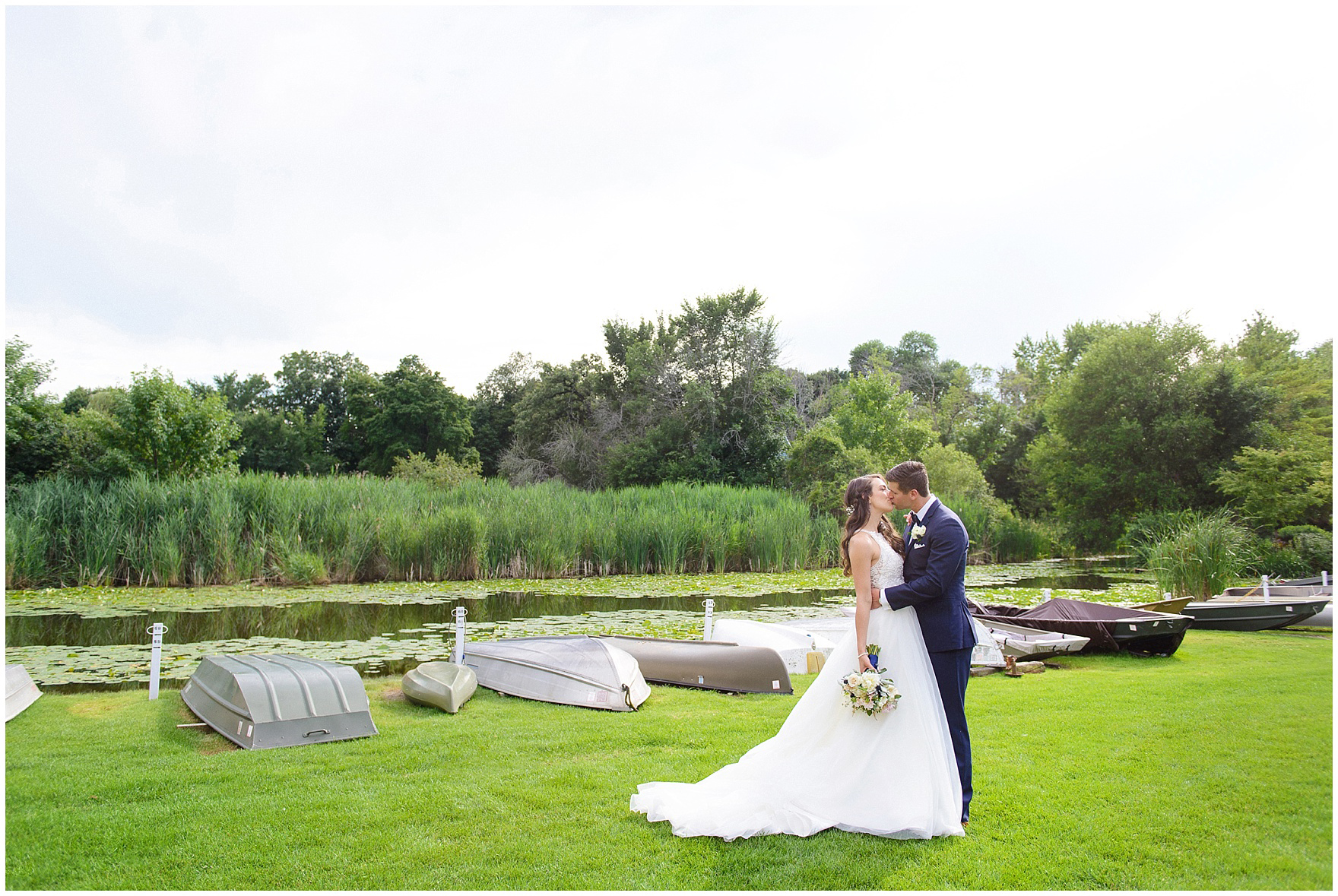 The bride and groom pose near the beach at Honey Lake during their Biltmore Country Club Barrington wedding.