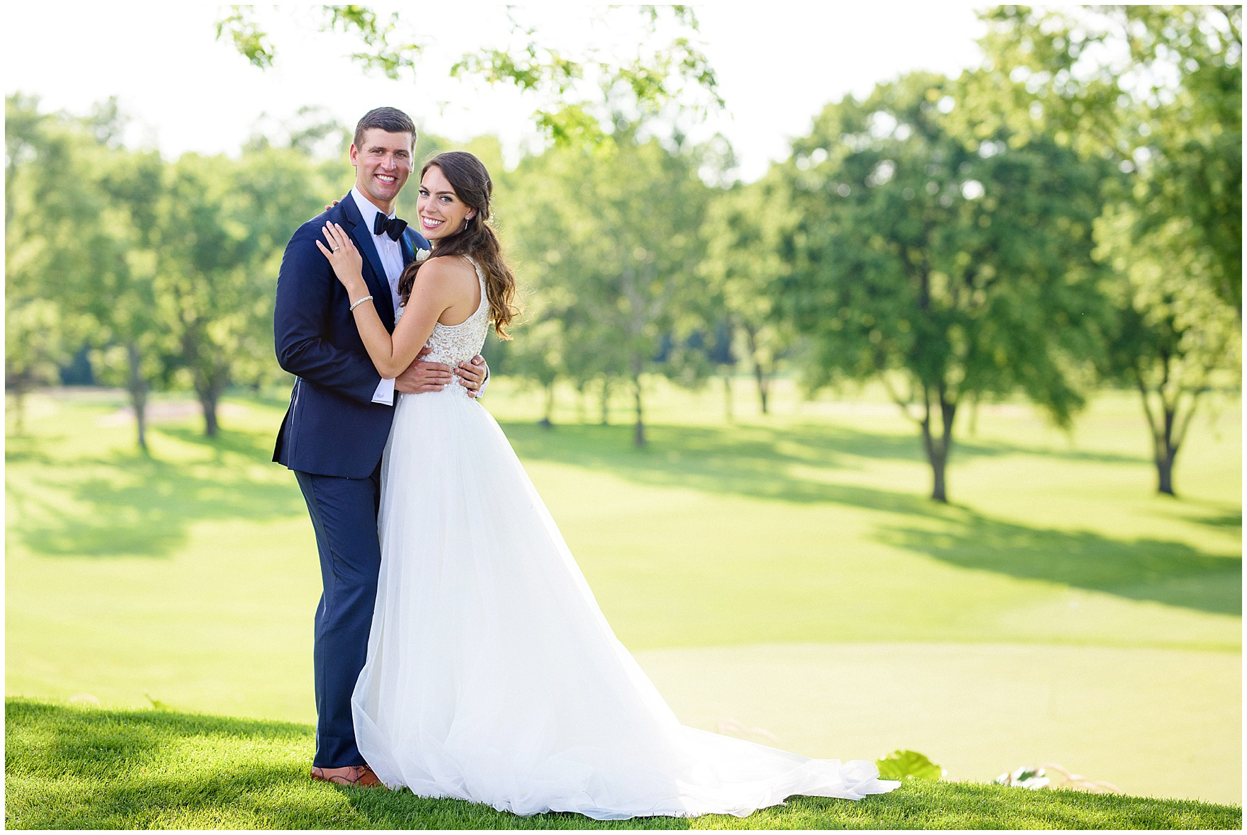 The bride and groom pose on the golf course during a Biltmore Country Club Barrington wedding.