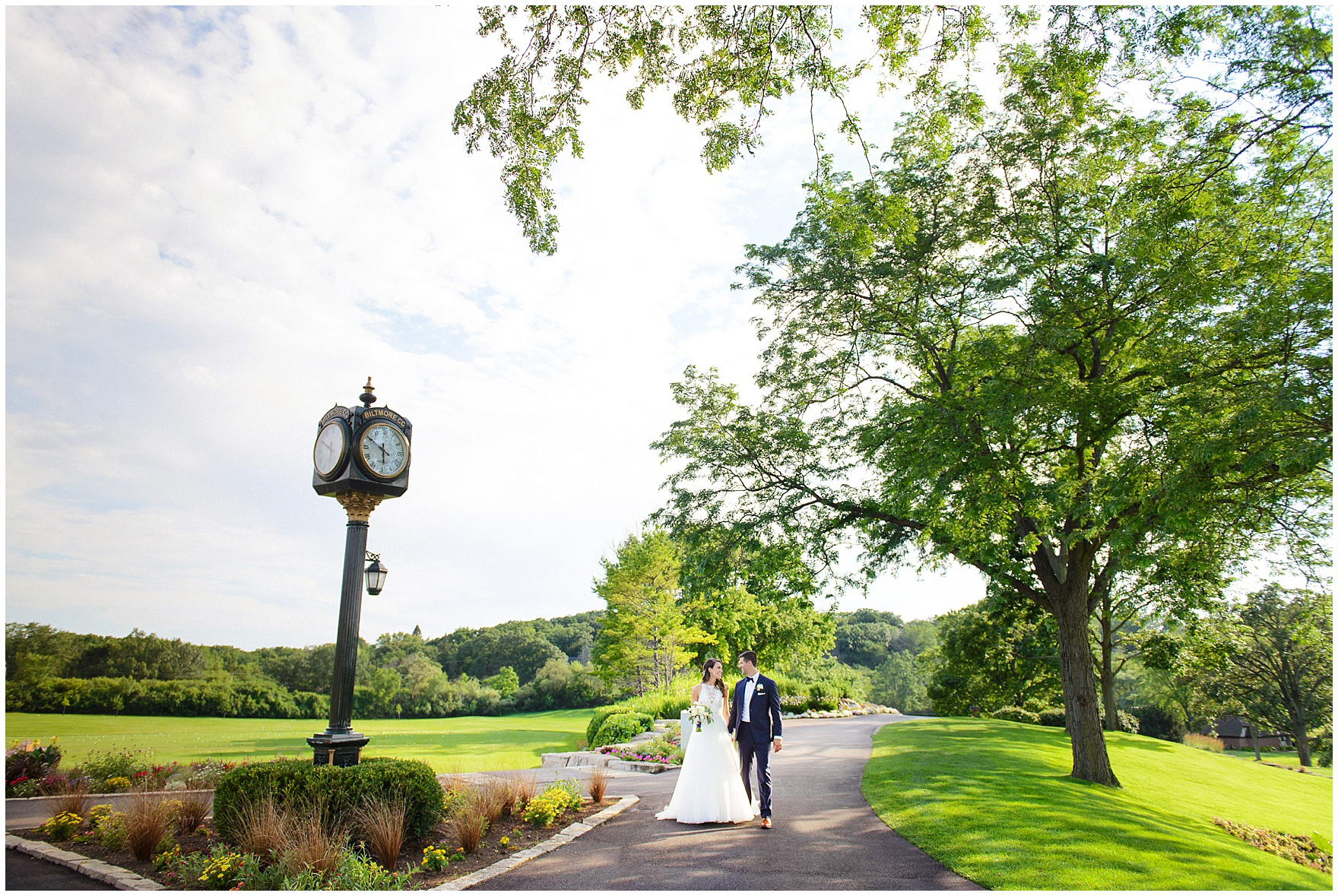 The bride and groom walk on the golf course during a Biltmore Country Club Barrington wedding.