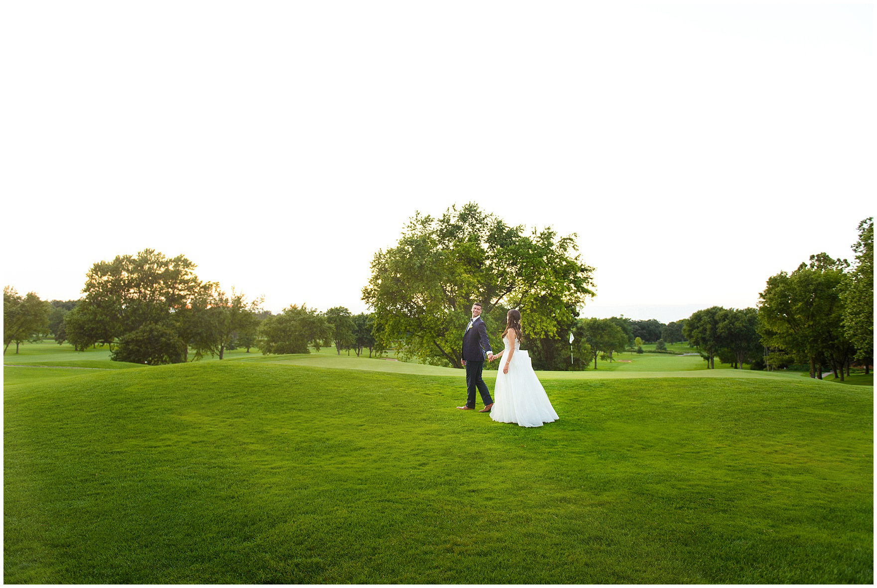 A bride and groom walk along the golf course at sunset during a Biltmore Country Club Barrington wedding.