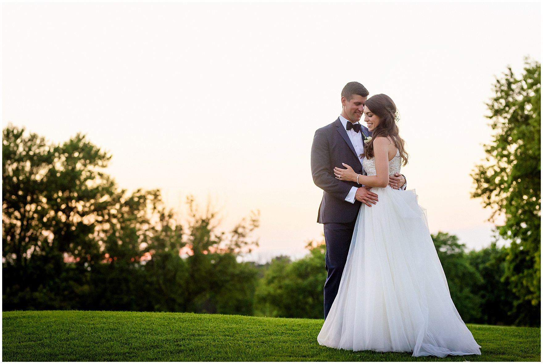 A bride and groom embrace on the golf course at sunset during a Biltmore Country Club Barrington wedding.