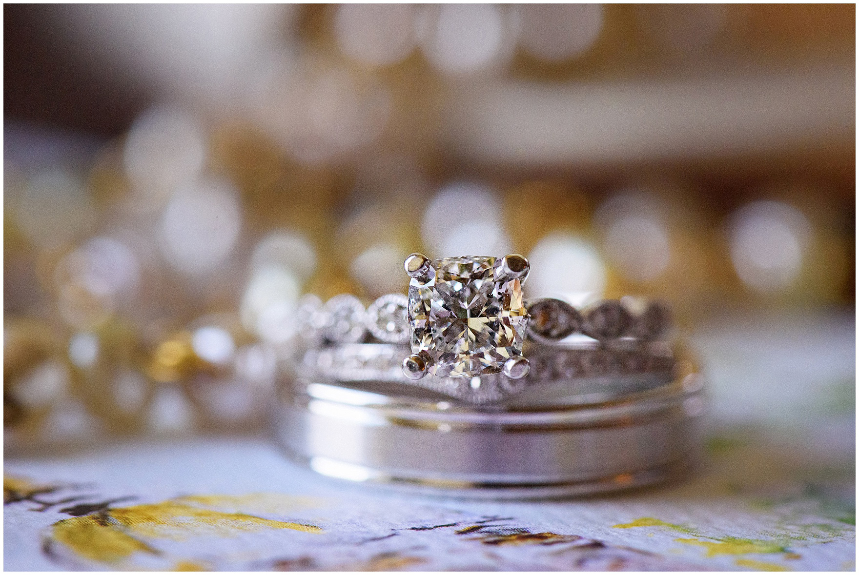 Detail shot of an engagement ring with wedding bands for a University of Notre Dame wedding.