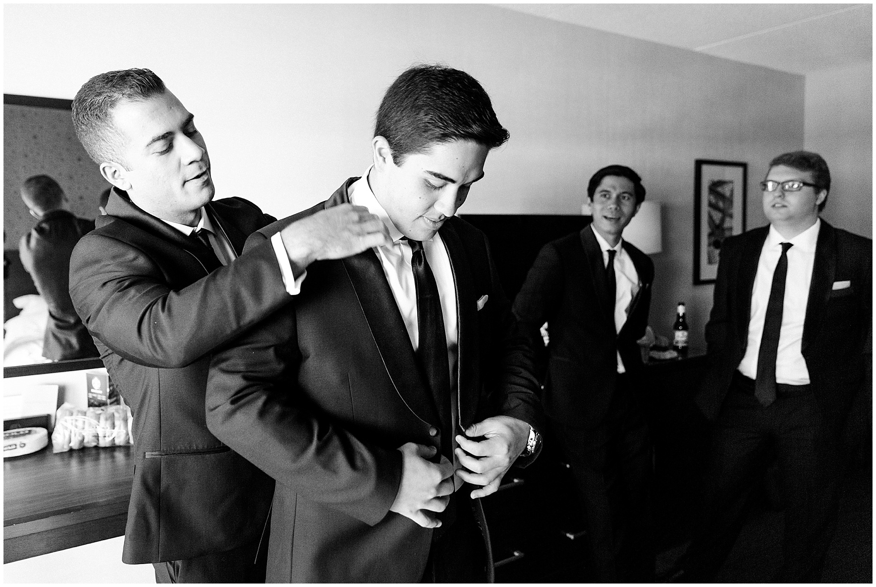 Groomsmen help the groom get ready for a University of Notre Dame wedding.