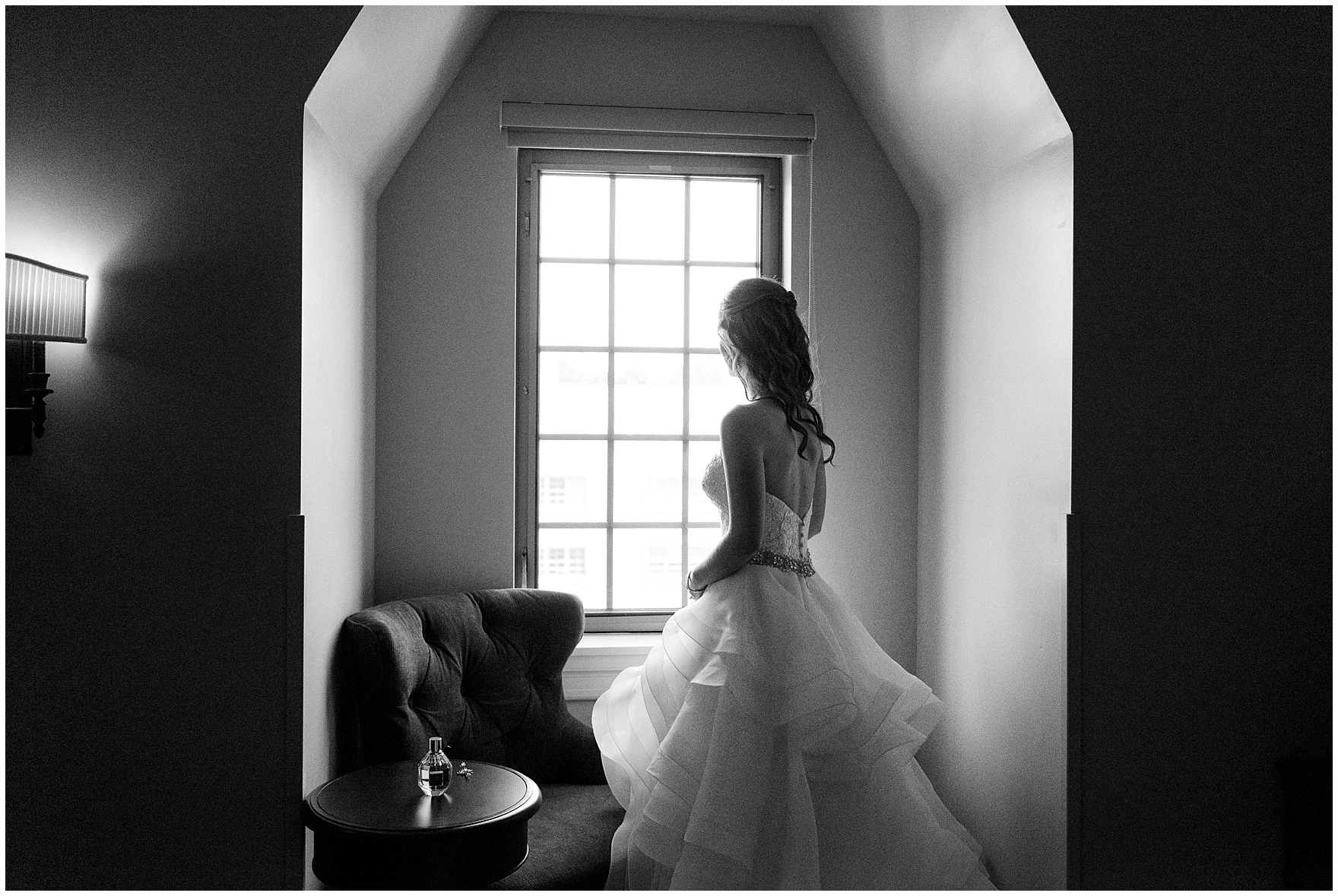 The bride stands in the window of her suite at the Morris Inn before a University of Notre Dame wedding.