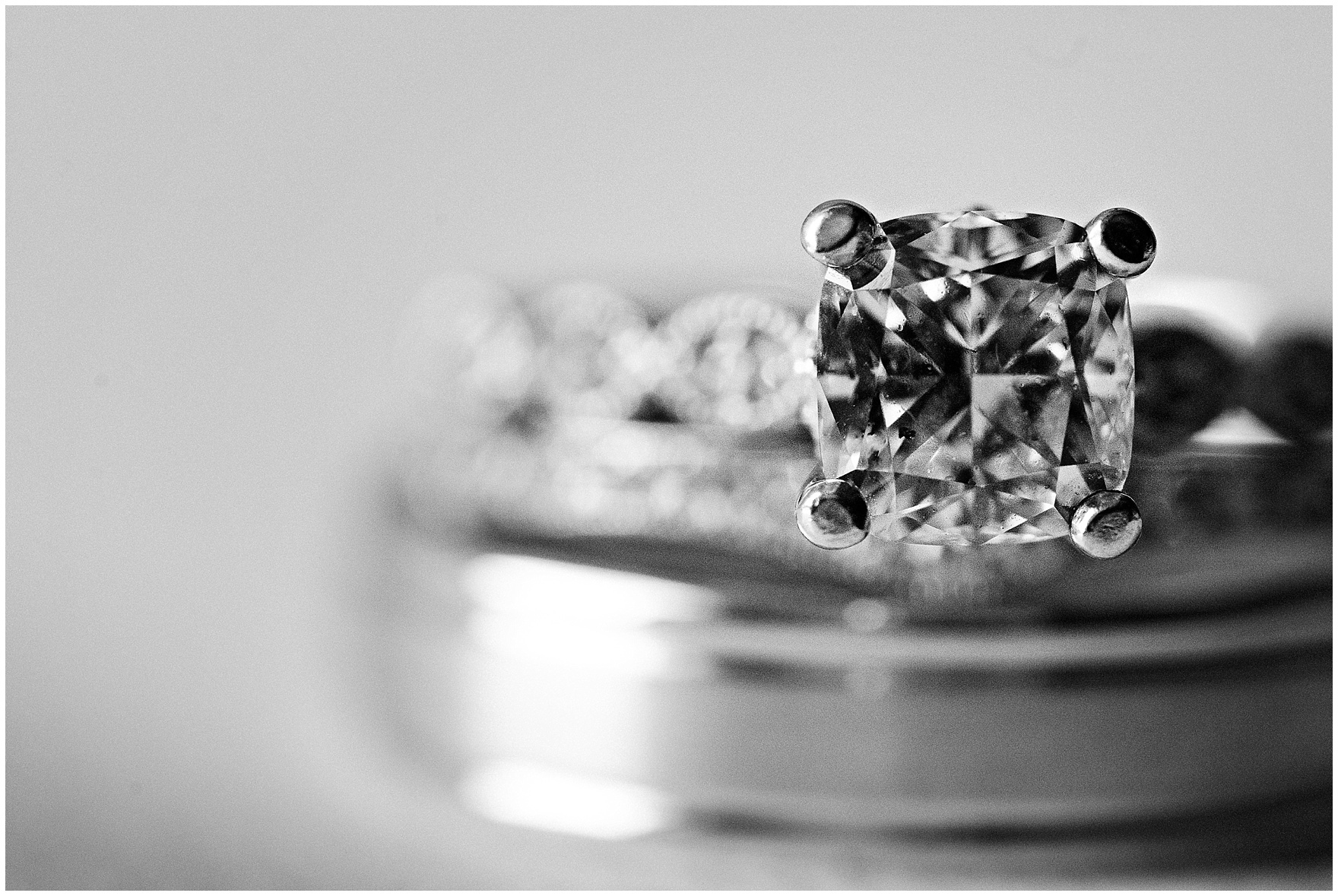 Black and white macro shot of an engagement ring and wedding bands before a University of Notre Dame wedding.