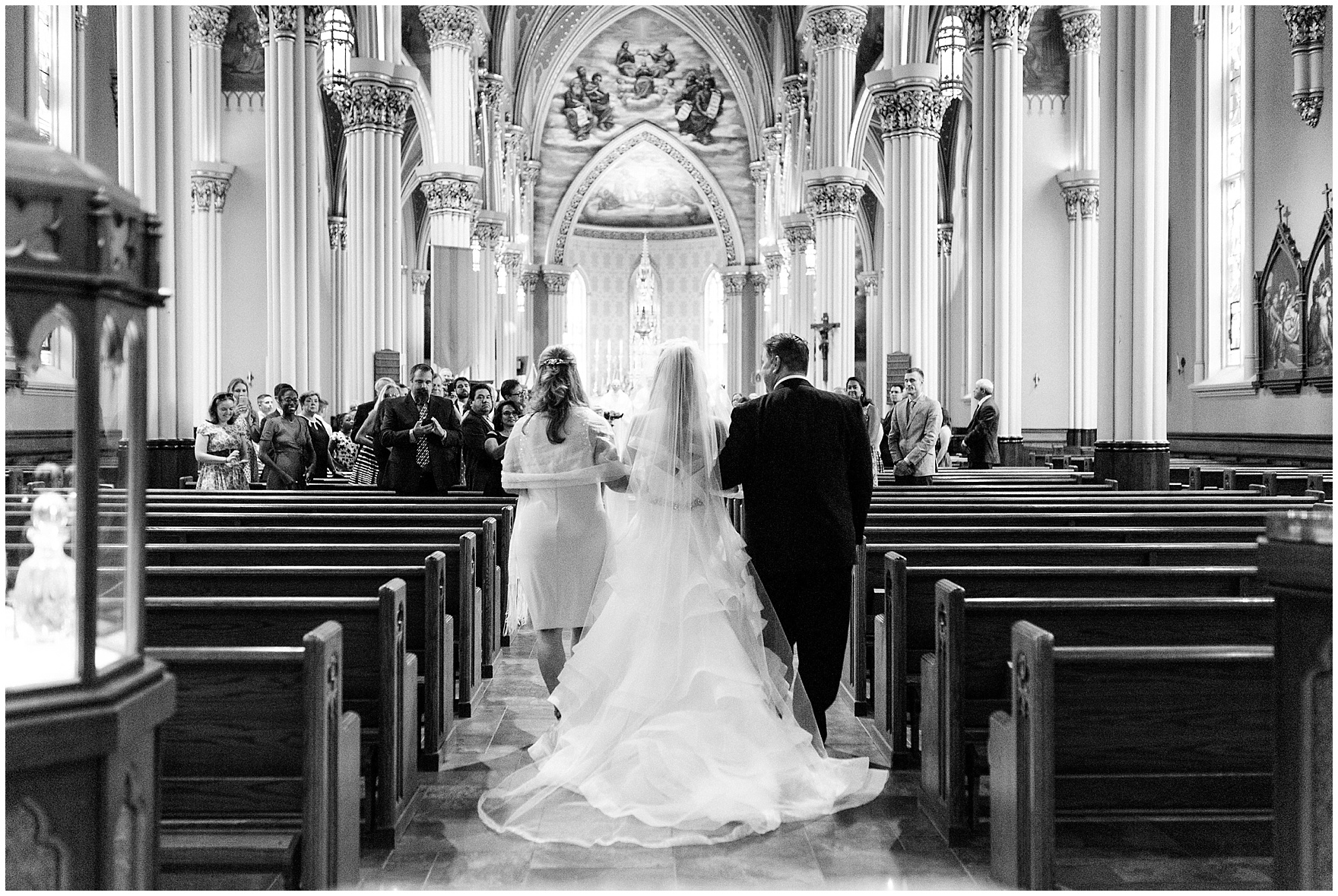 The bride and her parents walk down the aisle of the Basilica of the Sacred Heart during a University of Notre Dame wedding.