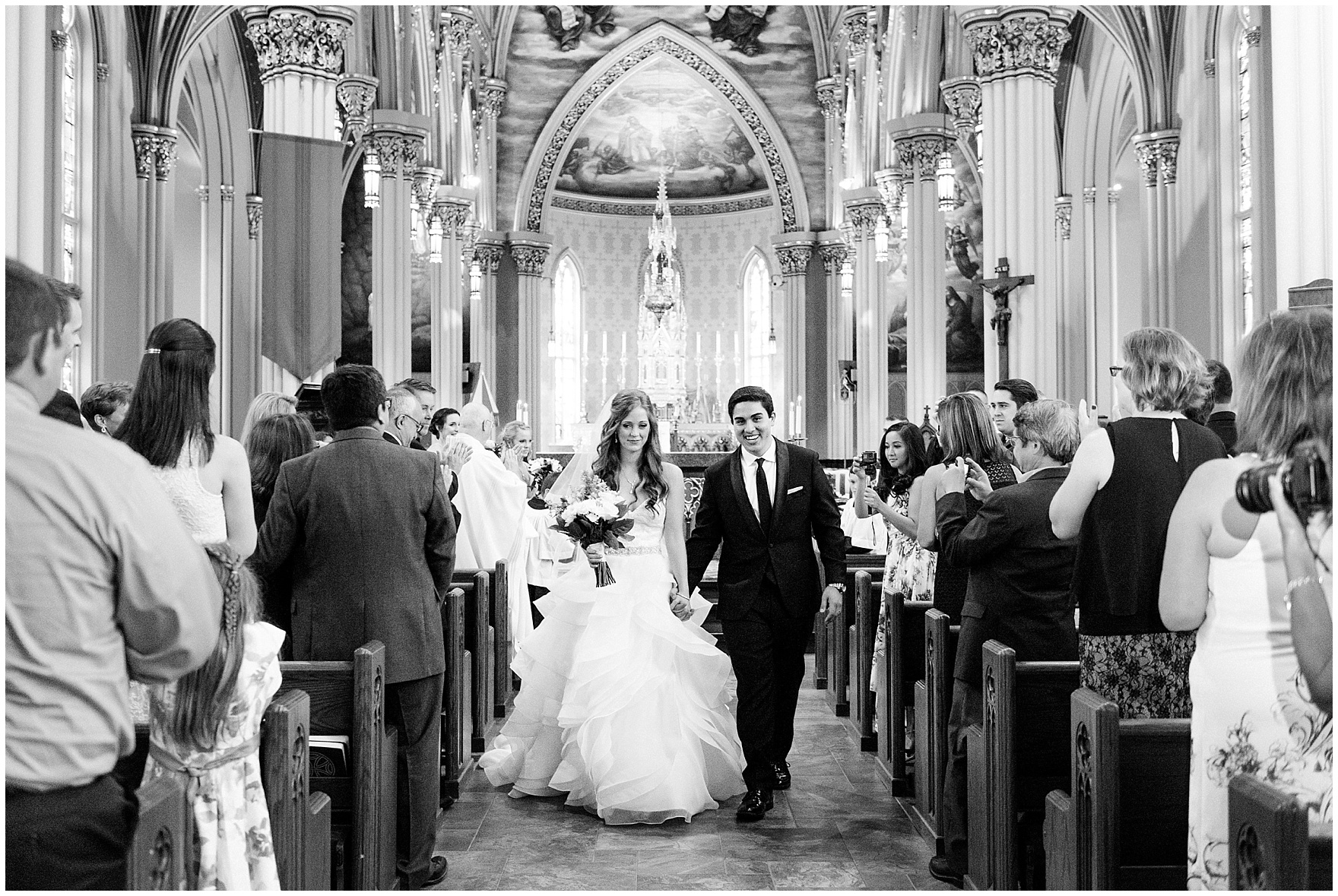 The bride and groom walk down the aisle of the Basilica of the Sacred Heart during a University of Notre Dame wedding.
