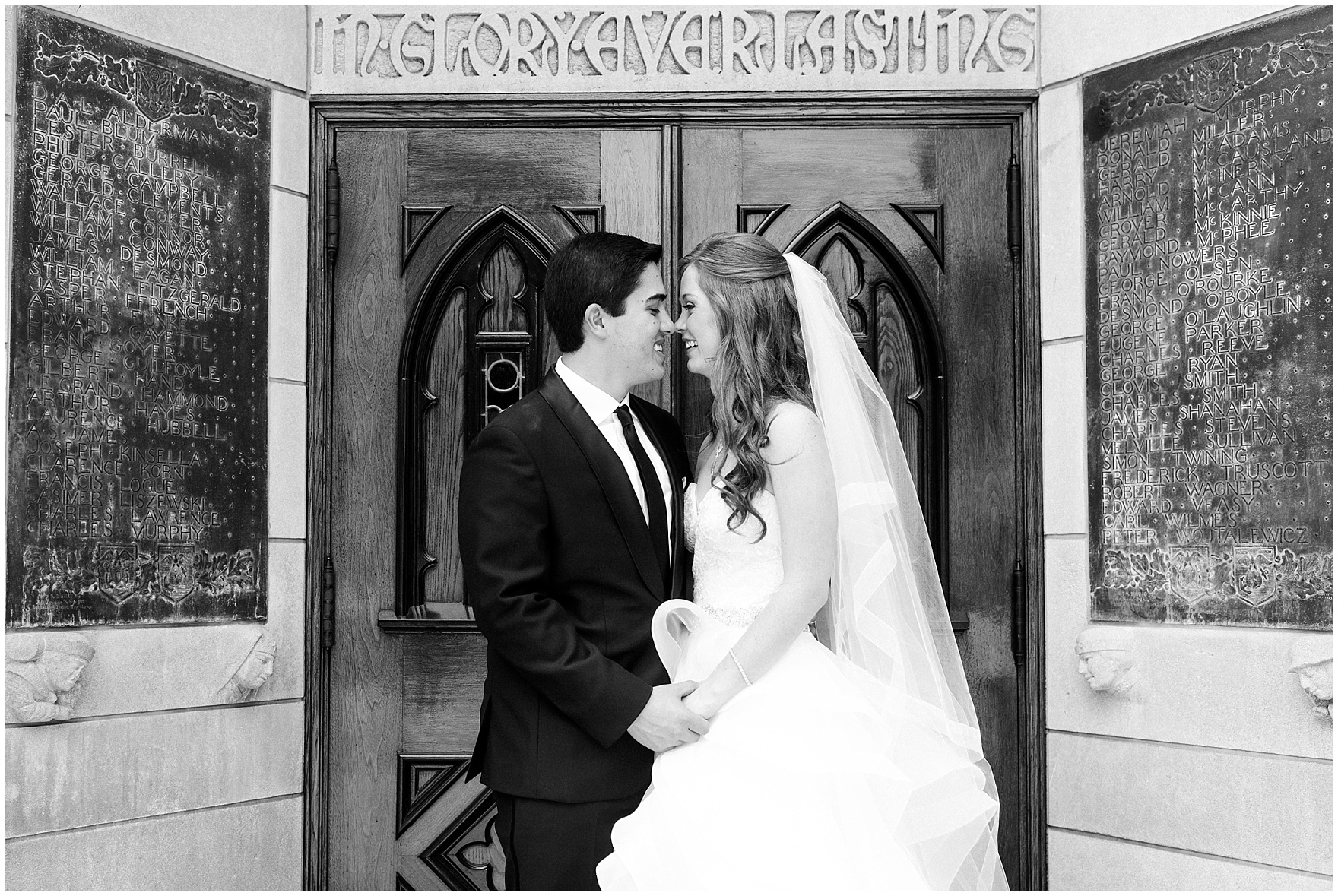 The bride and groom stand at the God, Country and Notre Dame doors of the Basilica of the Sacred Heart after their University of Notre Dame wedding.