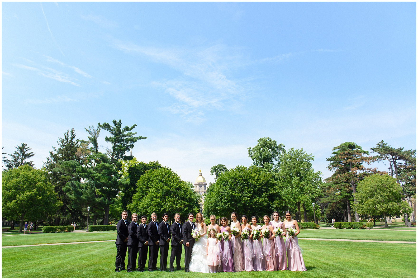 A bridal party poses for portraits on campus during a University of Notre Dame wedding.