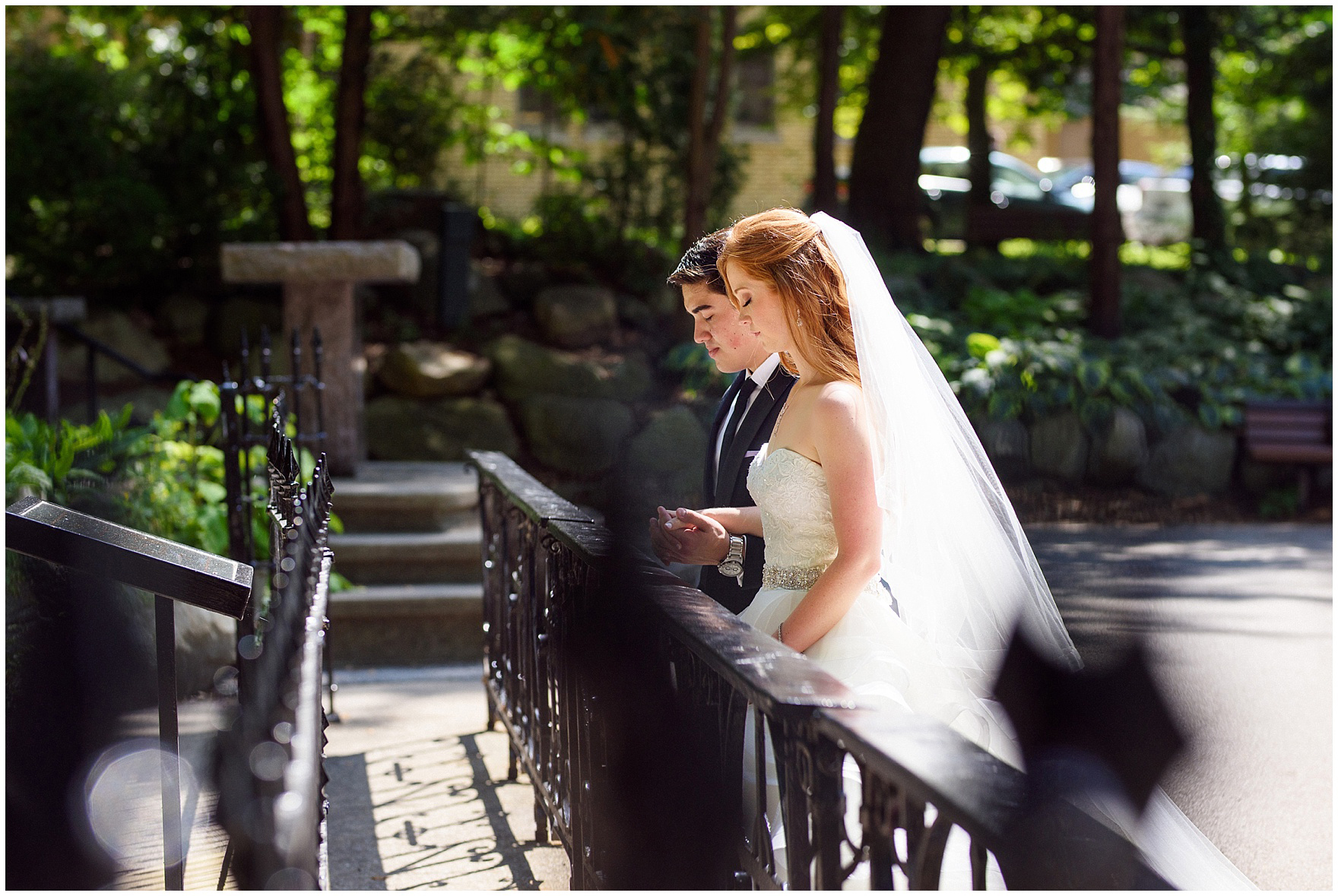 The bride and groom pray at the grotto during a University of Notre Dame wedding.