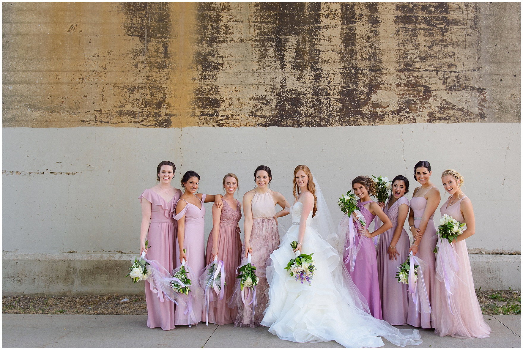 The bridal party poses under an old bridge in South Bend after a University of Notre Dame wedding.