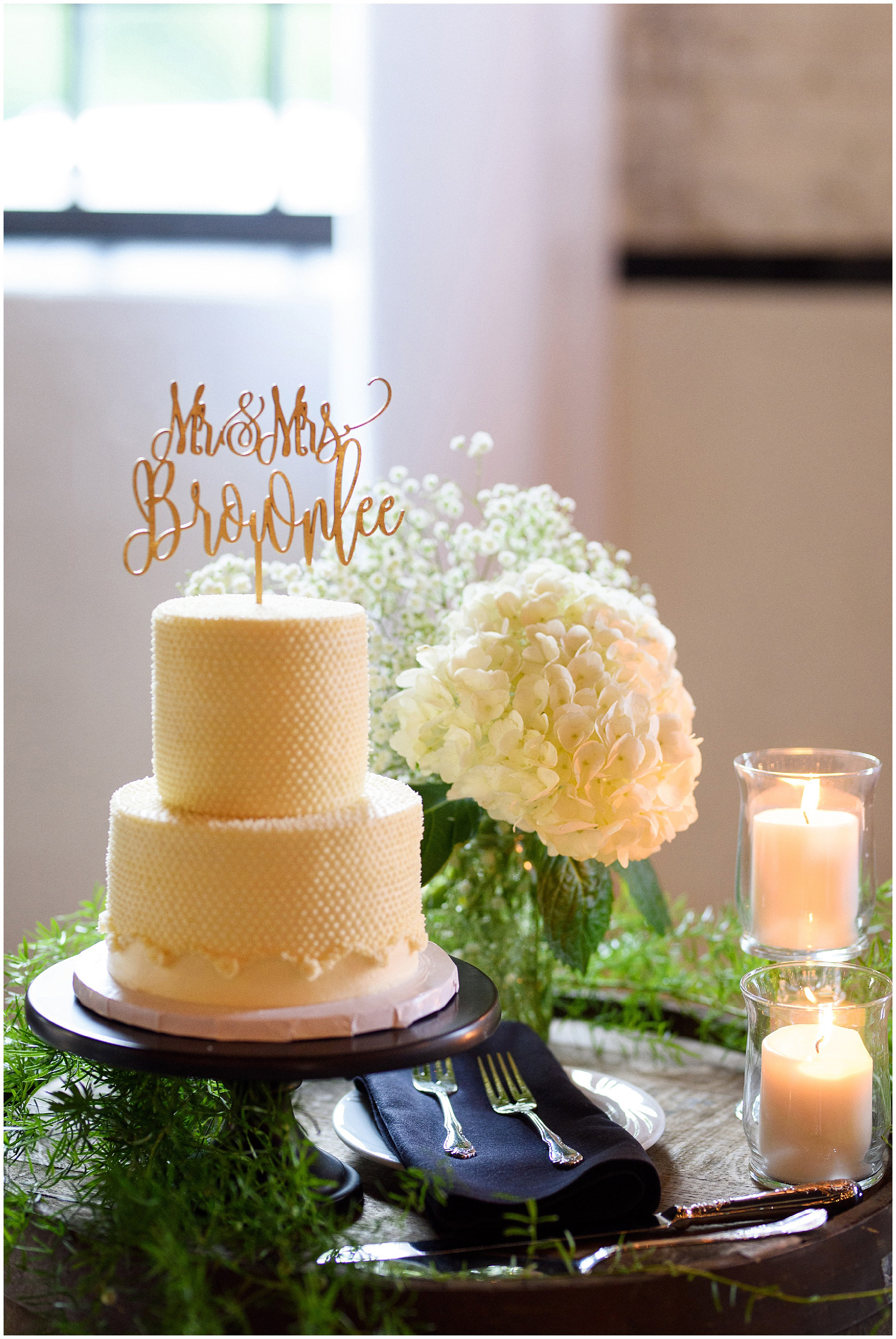 A two-tiered wedding cake by Magnolia Bakery with a personalized cake topper for a wedding reception at The Brick in South Bend, following a University of Notre Dame wedding.