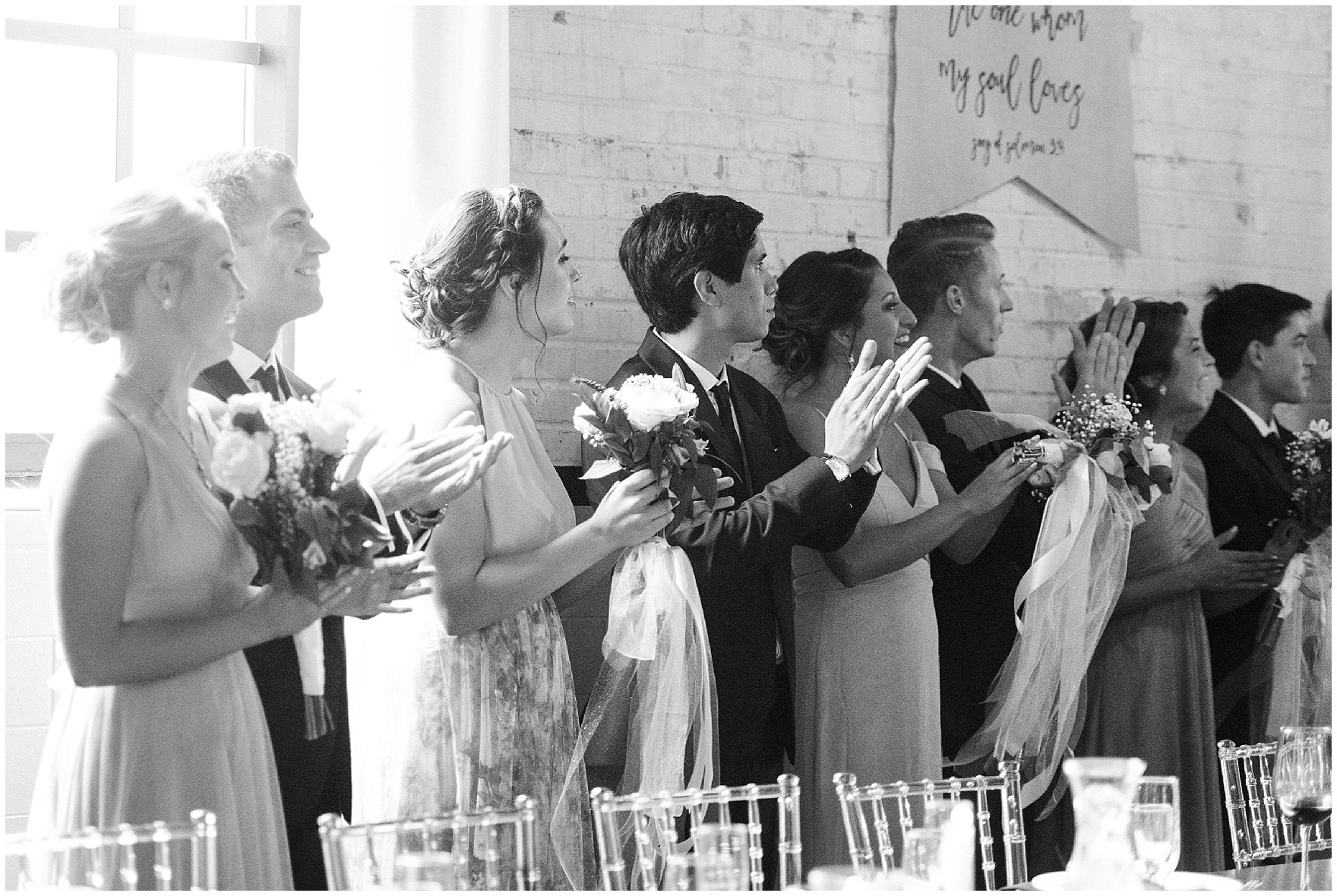 The bridal party cheers as the bride and groom enter their wedding reception at The Brick in South Bend, following a University of Notre Dame wedding.