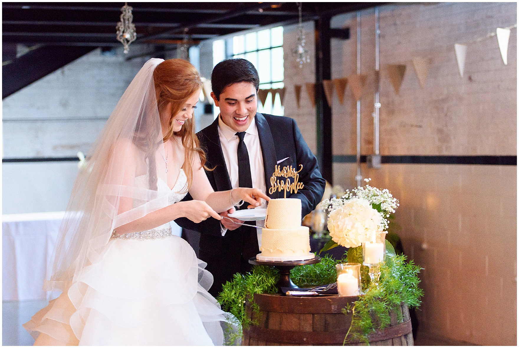 The bride and groom cut the cake during their wedding reception at The Brick in South Bend, following a University of Notre Dame wedding.