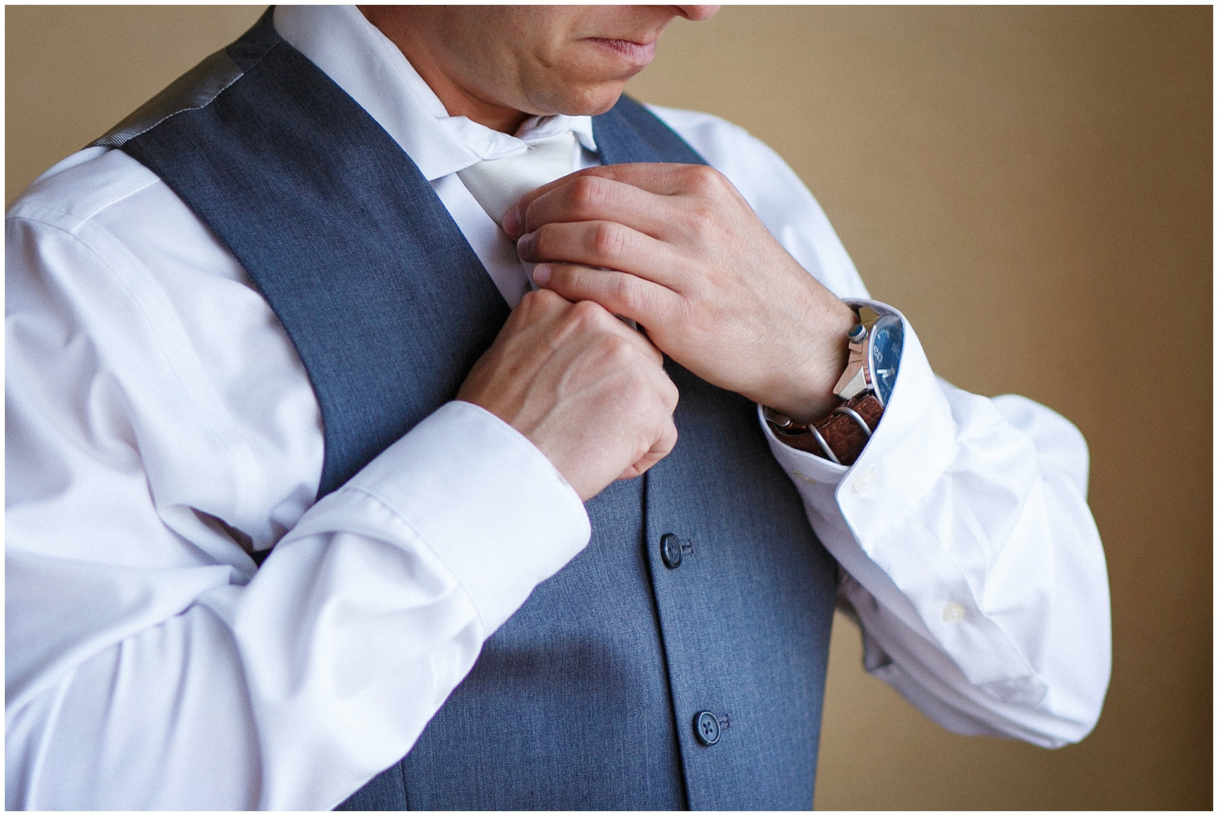 A groom ties his tie while getting ready for his St. Francis Xavier and Brookfield Zoo Chicago wedding.