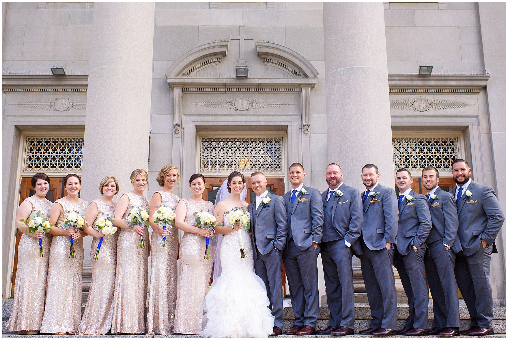 The bridal party poses on the steps of the church at a St. Francis Xavier and Brookfield Zoo Chicago wedding.