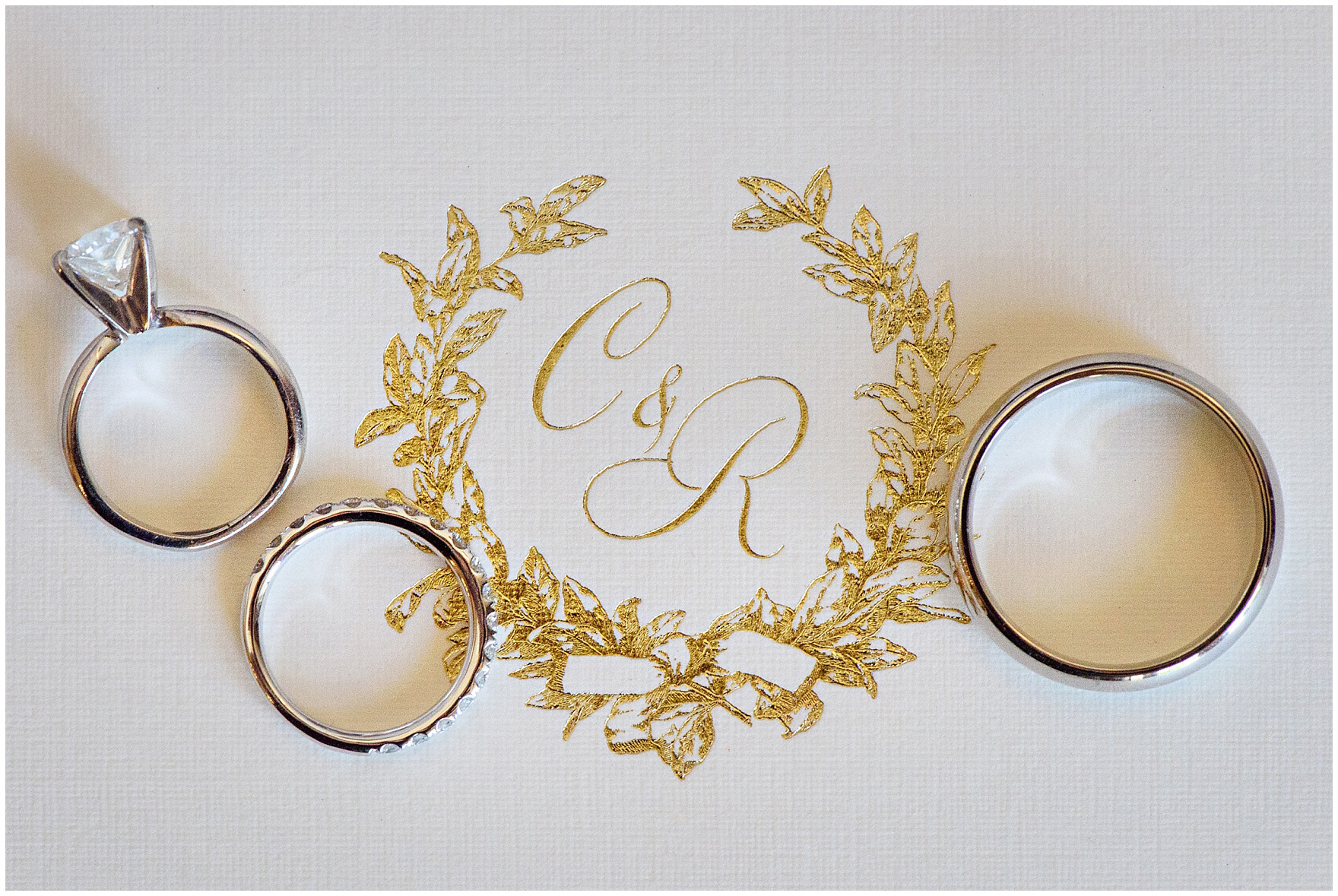Detail of a gold foil monogram on an invitation for a Butterfield Country Club wedding.
